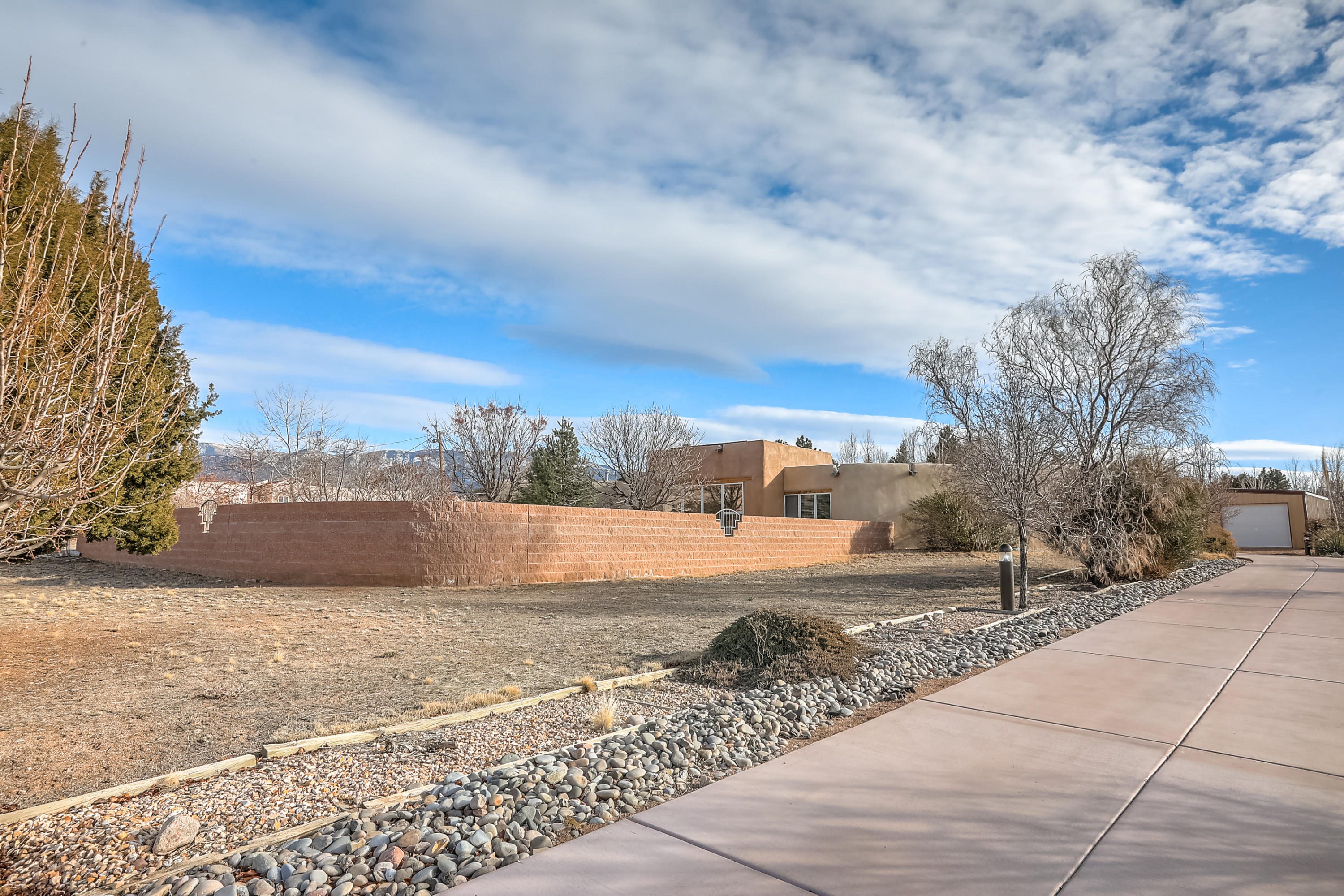 Welcome to this beautiful custom one story Adobe home in NAA w/stunning views of the Sandia Mtns. Southwest ambiance & luxurious appts include marble plastered walls, brick floors, beam & knotty pine ceilings, Pella windows & exposed abode walls. Foyer sitting rm, spacious living area w/wood burning stove, wet bar & picturesque windows. Updated cooks kitchen w/granite ctps, breakfast bar, hickory cabinets, Kiva fireplace & stainless steel appliances. Master suite w/2 walk-in closets, lg updated shower, soaking jetted tub. 2nd Master suite with 3/4 updated bath, Kiva f/p & walk-in closet plus roomy 3rd bedroom & hall full bath. Outdoor living for the whole family include a large covered patio, gated heated pool w/cover, 2.5 attached garage + Oversized 2CG/workshop, storage & solar panels!