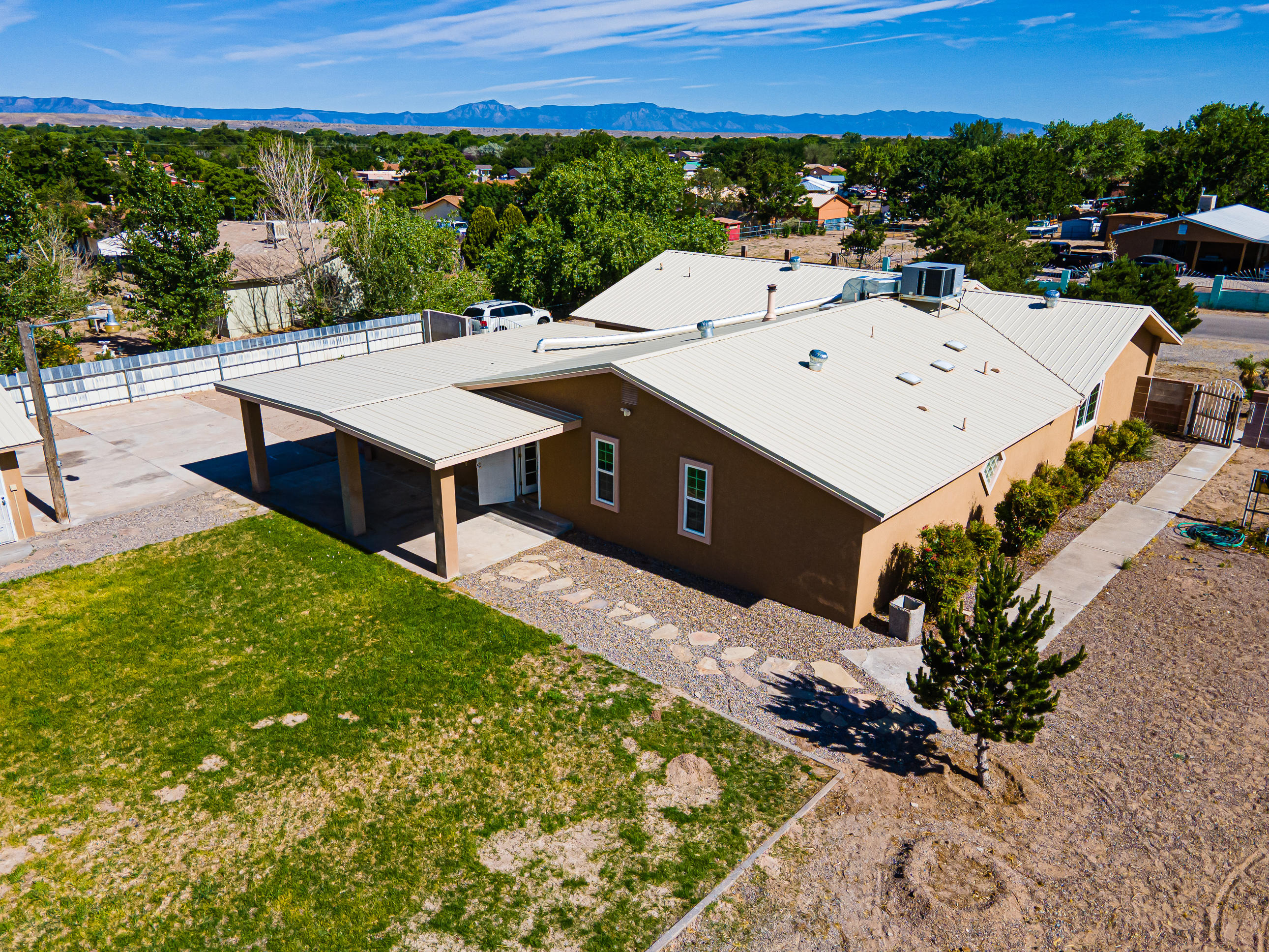 This single story beauty sits on 1/2 Acre lot with side/backyard access with 2 car detached garage with air conditioner (Evap). The home features newer metal roof (2018), refrigerated air (2018), updated windows (2018), synthetic stucco (2018), new paint, 3 Bedroom, 3 Living Areas or make the 3rd living area into the 4th Bedroom/Office/Bonus room. Home also features, updated light fixtures, lots of cabinet space and open kitchen with formal dining area. Kitchen comes with Stainless steel Appliances, Tile and laminate floors throughout and no carpet. Large master bedroom with garden tub and separate shower and Large walk-in closet. As a bonus, you have a front and back covered porch and landscaping that is easy to maintain. Call today for your private tour.