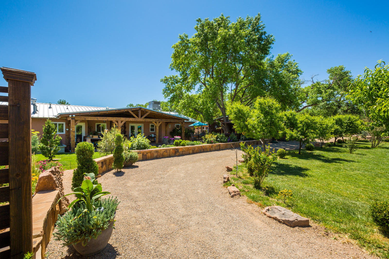 This stunning property is a dream come true for either equestrians, organic farmers or someone who wants to live on gorgeous  grounds that feel like a private botanical garden. Home sits on front 1.08 acre lot and has been beautifully remodeled. Since 2018, the owners have spent more that $220,000 in improvements. The back lot is 2.55 acres and a large home could be built on it, as it is separately platted. The horse facilities are top-notch and include 11 stalls, a wash rack and beautiful arena and pasture. The grounds feature an abundance of fruit trees, flowerbeds and vegetable gardens (all organic). Perfect for outdoor entertaining, there is a huge covered portal with beams and ceiling fan, a rock waterfall and bar. The beauty of these grounds will take your breath away.