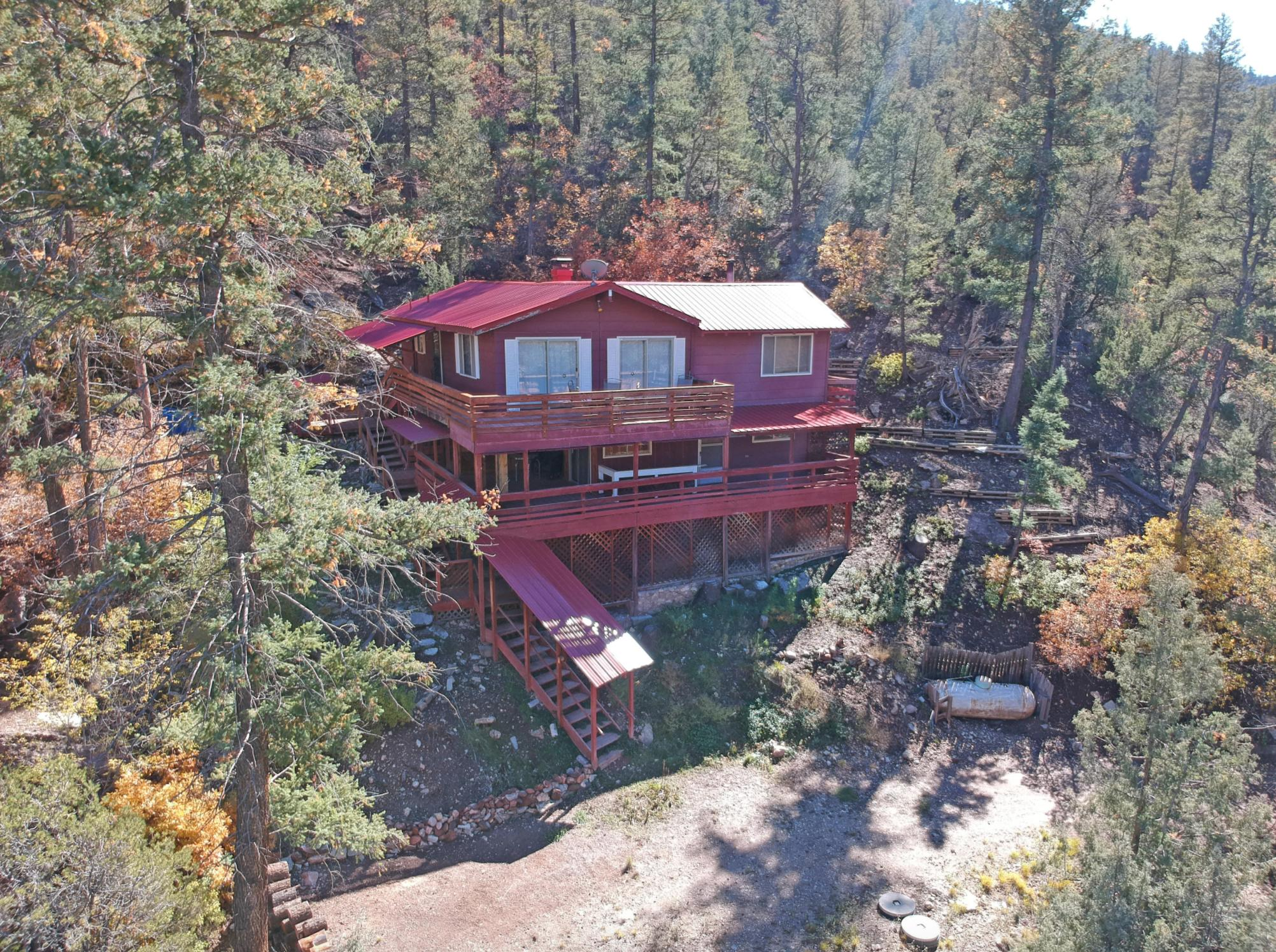 BACK ON MARKET - Relax in your very own 3 acre mountain oasis in the Jemez Valley! Conveniently located near all of the amazing outdoor opportunities Jemez is known for, and only a few minutes to the comforts of the village of Jemez Springs. Drink your morning coffee on either one of the two wraparound decks, surrounded by Ponderosa Pines and western mountain views. Meander down to the Jemez River for even more tranquility. With three bedrooms (and a possible fourth) and an open living area that provides versatility, this place is amazing for weekend retreats, or to make a year-round home. Vaulted ceilings in the living room and dining room and abundant natural lighting provides the serenity you're searching for. You'll love this one, especially for the price!