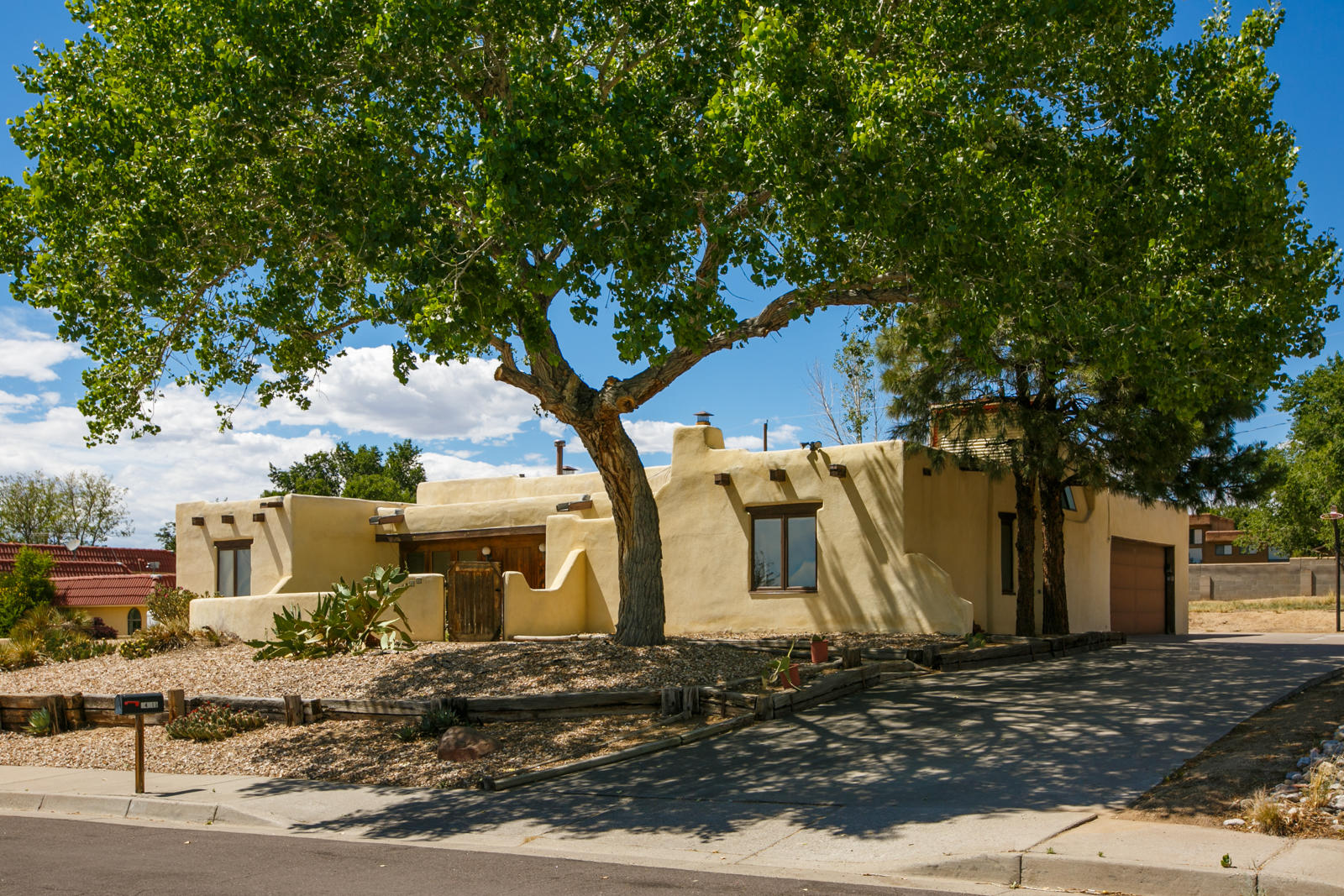 Take a look at this great Adobe home in a convenient NE Heights location. This property is loaded with Santa Fe charm including exposed adobe accents, gleaming brick floors, charming kiva fireplaces, beautiful beamed ceilings, and multiple private courtyards. There are 2 living areas, with a double sided fireplace separating them, a formal dinging room and a breakfast nook open to the kitchen, a large laundry room, and 4 bedrooms. The master suite offers a charming private courtyard and is in it's own separate wing of the house allowing for lots of privacy. The kitchen features handcrafted cabinetry and gleaming granite countertops. The backyard is huge and offers many possibilities for the next owner to customize to their liking. Convenient access to Sandia Labs, Kirkland, and shopping!