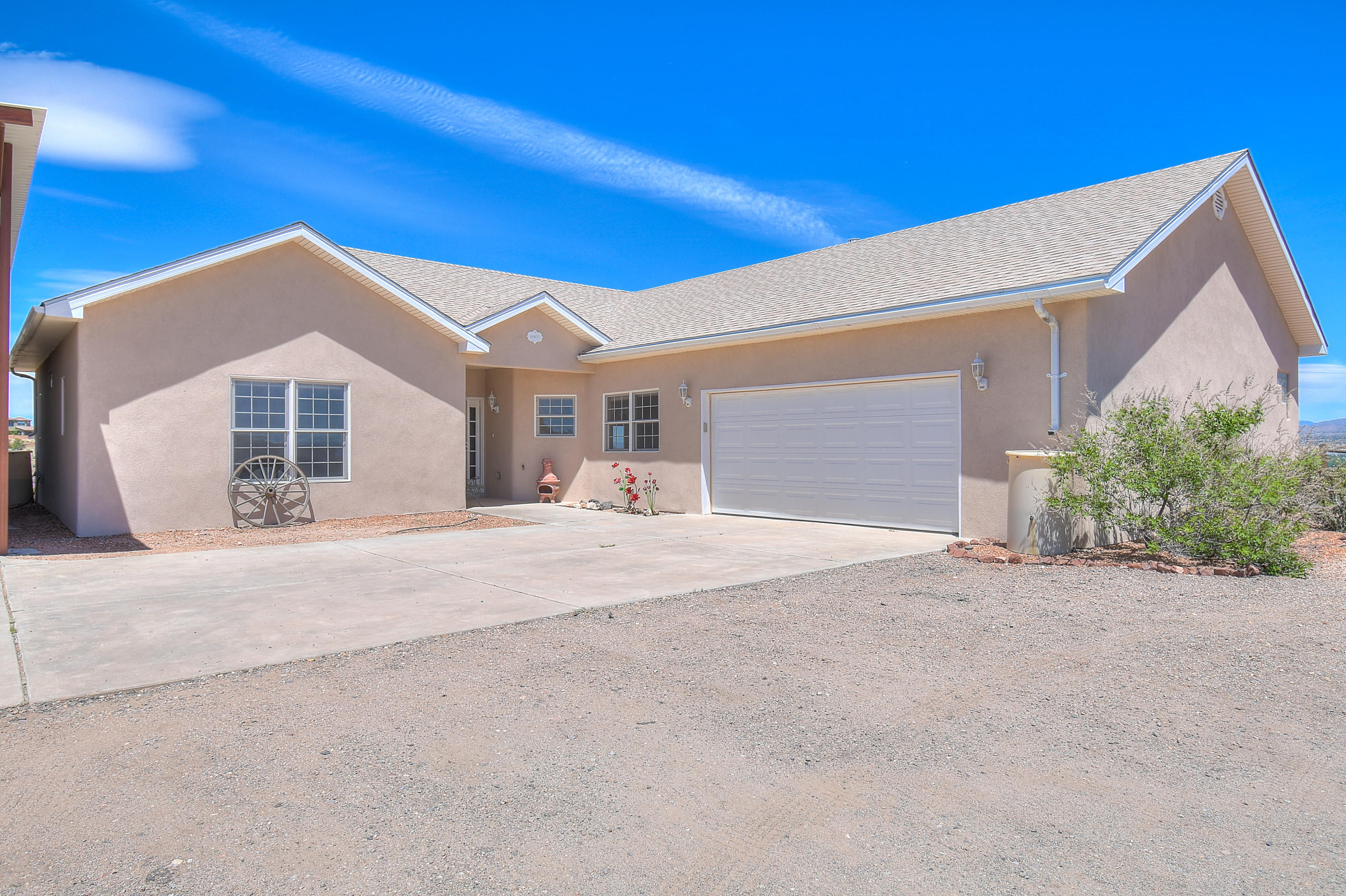 Come take a look at this custom 1 story home on half a acre.  Newer roof, stucco,tankless water heater and flooring. The house also has refrigerated air, raidaint heating and a massive deck off back yard. There is also a RV Pad with Hookups! What makes this house stand out in addition to the open floor plan is the Views! From the back deck you can view 5 mountain ranges: Jemez, Sangre de Christo, Ortiz, Sandia and Manzano. Each day  listen to the sounds of nature and the almost interrupted by the quail and roadrunners that frequently visit the yard. The landscape has been completed in front and back yard with a amazing rock wall and sitting area. Come make this your Dream Home Today!!