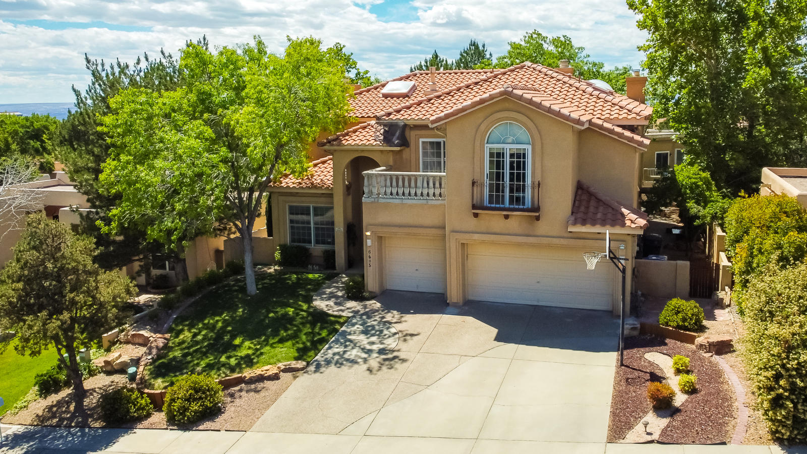 This beautiful custom home is nestled in a quiet cul-de-sac in Tanoan East, one of Albuquerque's most desirable communities.  Enjoy the privacy and security of this premier 24 hour guarded and gated community. This home is conveniently located just minutes from the Country Club as well. Inside, it has been beautifully updated and features a bright and open floor plan. On the main floor, there are 2 living and dining areas, a nicely updated kitchen, a grand foyer with a sweeping staircase, an office, and a bedroom with an en-suite bathroom. Upstairs you will find a beautiful master suite with a private balcony, a large bathroom and a walk in closet. There are also 3 additional bedrooms upstairs with another bath. The large backyard is nicely landscaped with grass and mature trees.
