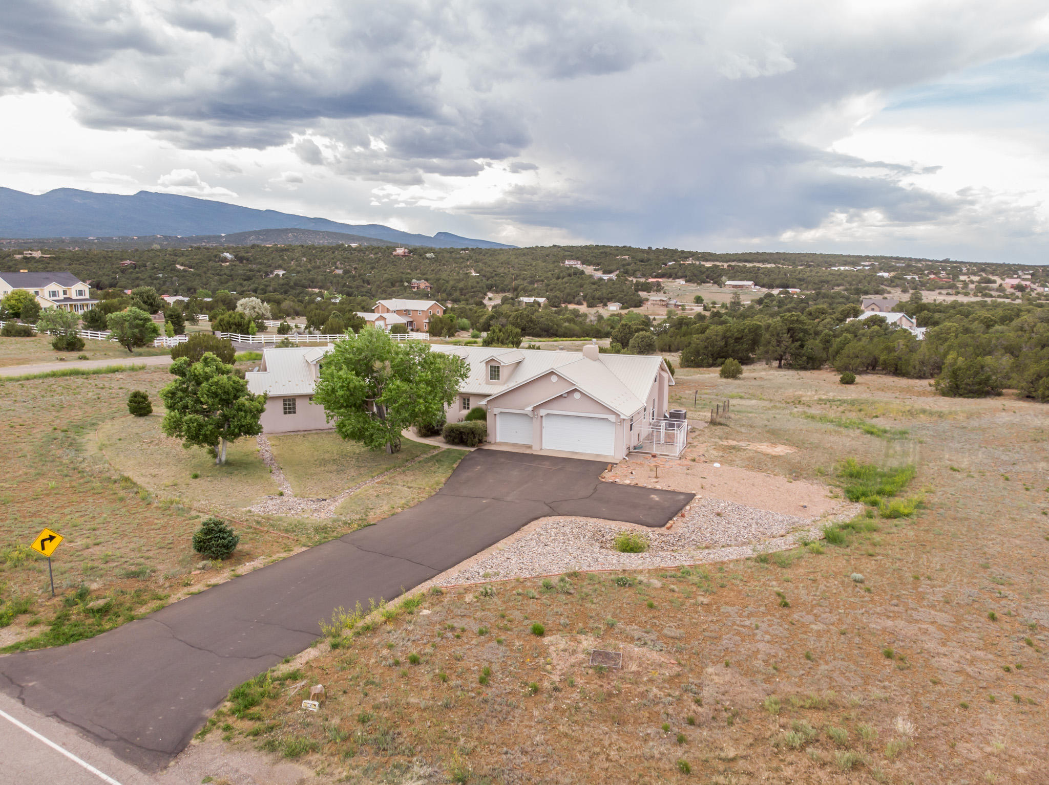 Absolutely delightful Northern New Mexico style home on 3 acres in the desirable Richland Estates neighborhood.  Soaring ceilings flood this home with beautiful light.  Flowing open floorplan that leads out to a grassy private covered patio with sweeping views of the Sandia Mountains.  Large kitchen with custom Halbert cabinets and island open to the dining room with tasteful posts and corbel accents.  Split floorplan and spacious master suite with kiva fireplace, jetted tub and large WIC and shower.  3 bedrooms, plus an office with glass french doors and kiva fireplace.  Large picture windows, tasteful tile plus custom tilework in the bathrooms and newer carpet. Metal roof, community water, No HOA and 3 car garage.  Don't miss this home, it's a beauty!  *Virtual Tour in photos tab*