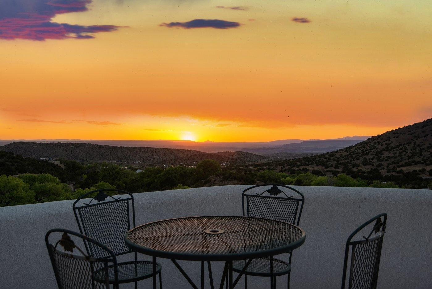 Nestled in the foothills of beautiful Placitas, this stunning custom-built home offers breathtaking, one-of-a-kind views of Cabezon peak, the Rio Grande River Valley, and the Sandias. A private and tranquil sanctuary that features rounded window walls and magnificent viewing decks to capture the spectacular views that surround this captivating property. Beginning with its gated courtyard entry and continuing throughout the home, the builder's masterful architectural details, including vigas and beams, are spectacular! This magnificent property features a formal living area with a kiva fireplace; a formal dining area with a coved beam ceiling and gorgeous hard wood floors; an open concept family room integrated with a spacious kitchen featuring granite countertops and spectacular