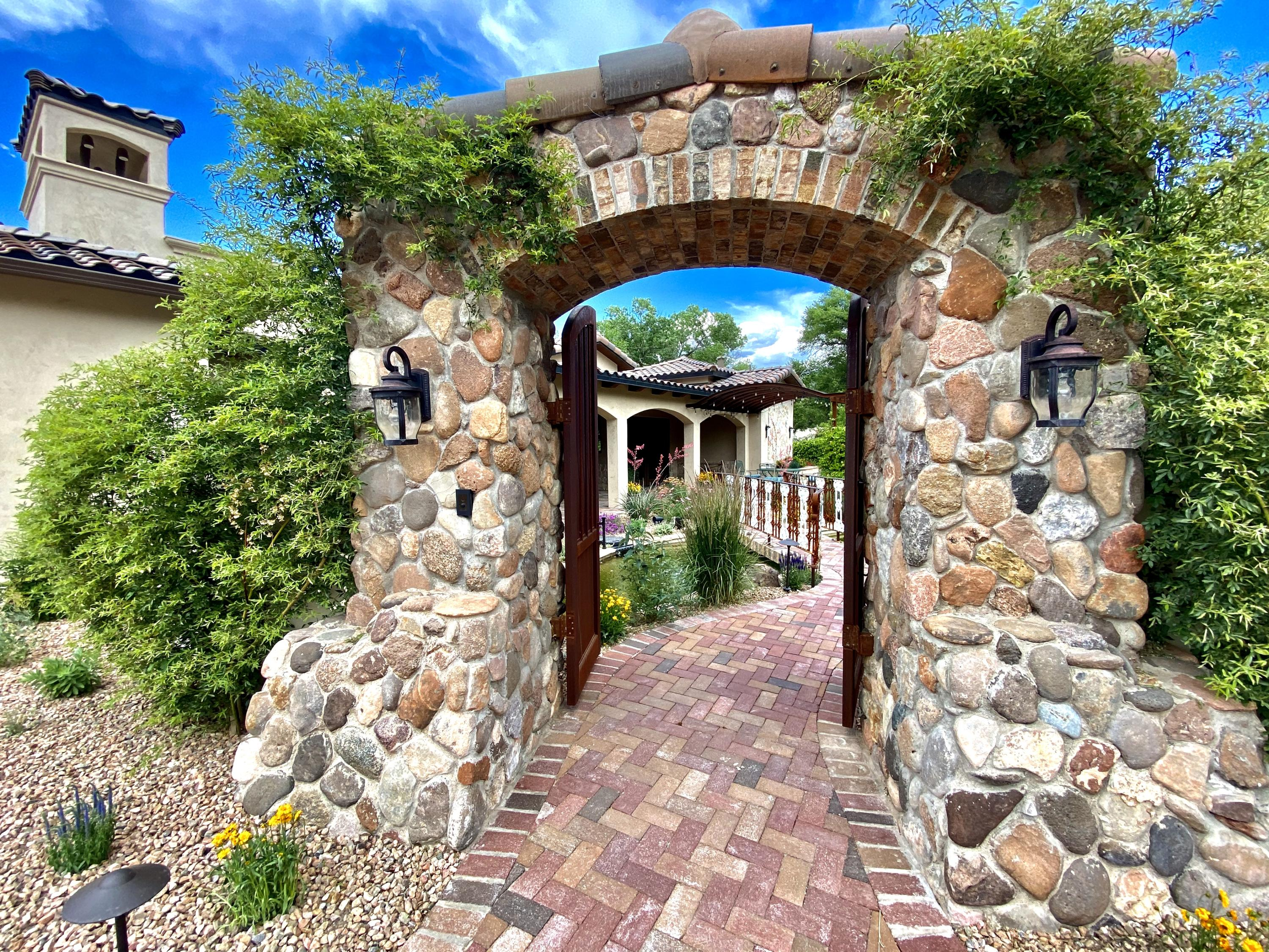 Experience tranquility...and retreat to your own peacefully private oasis nestled in Albuquerque's beautiful North Valley!  This Award-Winning Mediterranean European-style Green Built ''Gold Certified'' home is loaded with amenities and high-end custom finishes.  Enter through the gated stone archway into a private paradise with large pond, rock waterfall, lush landscaping, a bridge that leads to exposed brick patios and outdoor dining under the open air trellis.  A masterful blend of European flare with rustic, contemporary and industrial elements are combined with a soothing color palette and an intriguing blend of finishes and materials, including imported French limestone and Indian walnut wood flooring throughout, stone arches, and East-facing European Farmhouse kitchen with custom