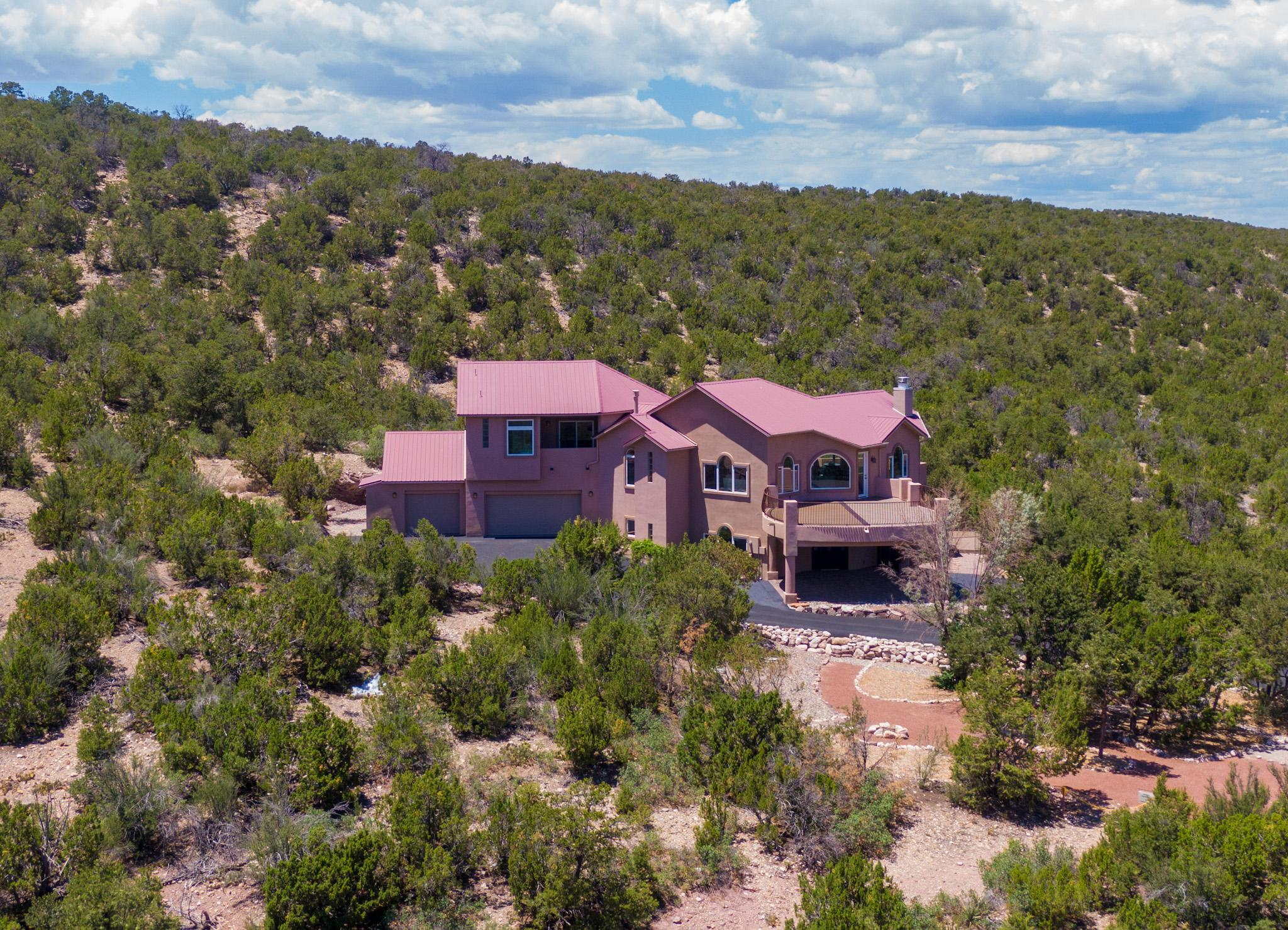 PRIVACY WITH TRUE LUXURY! Available for immediate occupancy! Please take the virtual tour! Looking for the perfect New Mexico  retreat? Only 12 minutes from retreat to  Interstate Highway 25, 45 minutes to the Albuquerque Sunport, 35 minutes to the Santa Fe airport. This beautiful home offers a tranquil and private mountain setting and is the last estate before the Cibola National Forest on two sides of the property. This truly unique home has a landscaped entrance, low light pollution for night skies and is nestled within 5 acres that lead into miles of National Forest and Sandia Crest hiking trails, surrounded by amazing views. 300 days of sunshine allow for stunning nightly sunsets and rainbows in the fall.  Prior to  entering this home, take a walk through the Native American Spirit