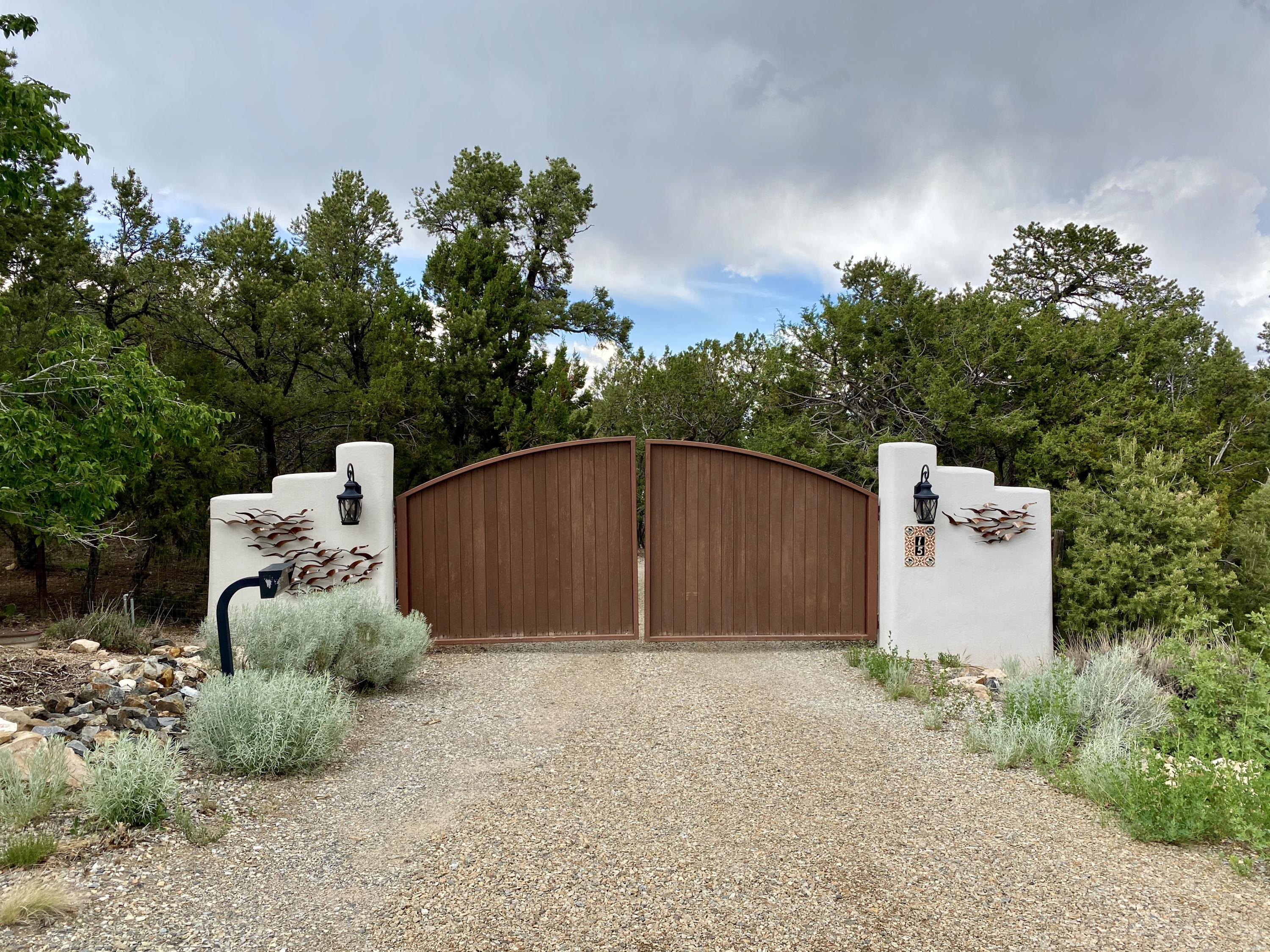Private gate leads to 1.5 fully fenced acres. Through the trees you'll see the beautiful hacienda w it's Gated Courtyard. Nestled on a premier view lot that backs up to open space this home is poised to capture mountain vistas & big blue NM skies! Upon first entry you're greeted with high ceilings treated w T&G, Beams, Vigas, Corbels, Nichos & Cedar planks. Living & dining rooms each have walls of french door windows under covered patios-perfect for entertaining. Remodeled open kitchen w KitchenAid professional appliances + plenty of cabinets & counter space. Master wing w Study, Kiva FP, beamed ceiling + ensuite bath w jet tub, sep shower, 9' vanity w 2 sinks. East wing w 2 bedrooms  (one w private entry) & den all have beamed ceiling accents. Award winning BY landscape design is perfect!
