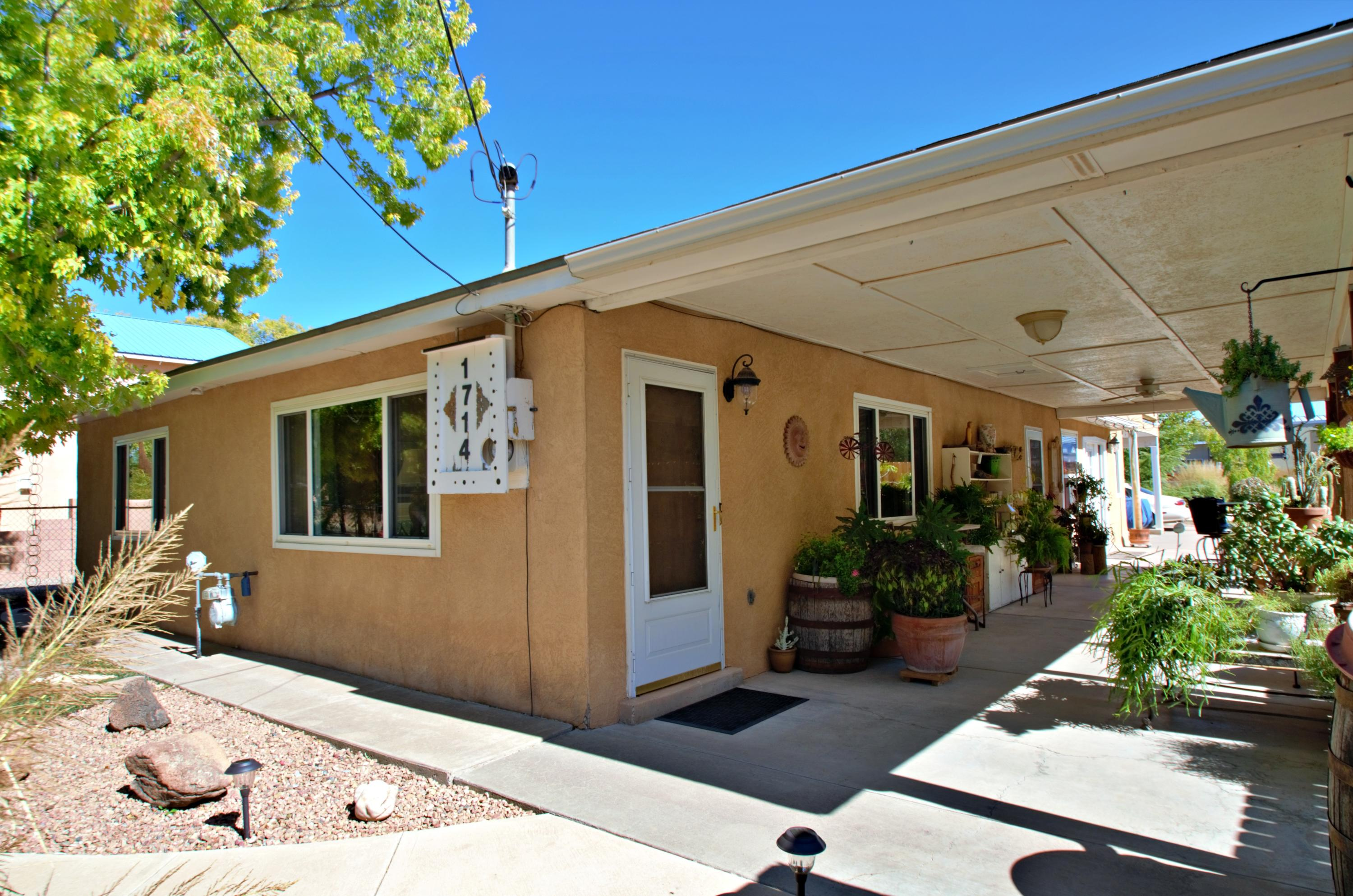 Price Improved! Charming, near North Valley home approx. 2490 sq.ft. living space and a large covered porch with ceiling fan for outdoor fun. Carport and adjacent area large enough for 4 vehicles. House sits on just over a 1/4 acre, with multiple mature trees and lots of room. Situated on a quiet street near a park and community center and within walking distance to the Bosque. Close to Old Town and Nature Center, easy access to I-40, and still quiet enough to feel remote. New cedar wood fencing on south side of property installed. All major kitchen appliances stay including a newer refrigerator, microwave and a new dishwasher. 2 large living areas, 4 nice sized bedrooms with two walk-in closets and a small balcony off the master. All bathrooms remodeled. Lots of storage! Come see this one