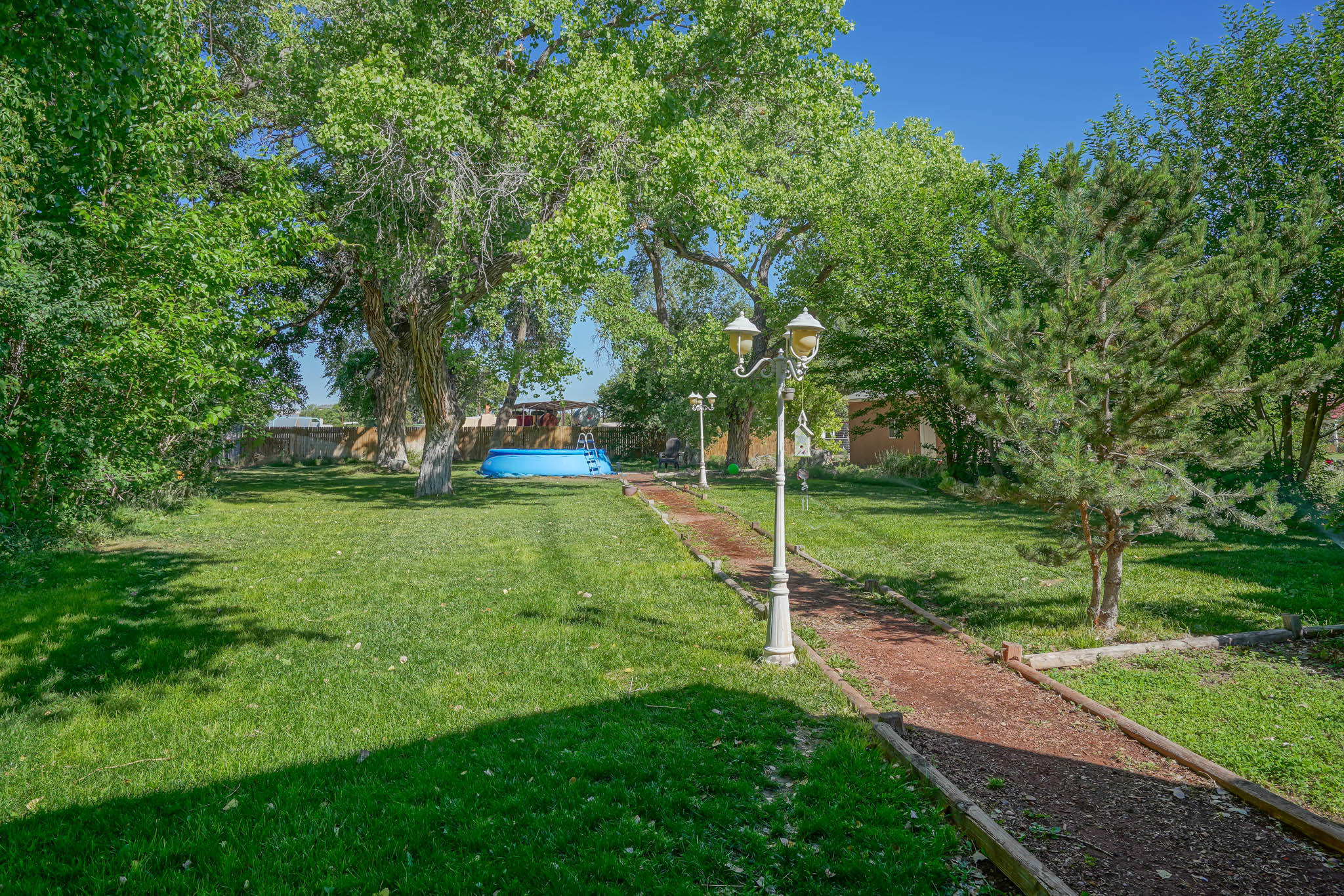 Have you been looking to get away from the city? This beautiful custom home in the heart of Los Lunas sits on .66 acres has what you are looking for. Built-in ''Nichos'' throughout the home, soaring ceilings and lots of natural light are just a few of the extras your new home has to offer. Enjoy cooking your favorite meals in the chef's dream kitchen with sile stone countertops and stainless Steel Appliances! The master bedroom opens up to a stunning park-like back yard with huge mature trees providing ample shade & a private jacuzzi hot tub. Sprinklers & drip systems are on an Irrigation well. A real gem in the heart of Los Lunas! There is also a detached workshop and four-car garage for extra storage and lots of room for toys! Take a virtual walkthrough tour or schedule a private showing