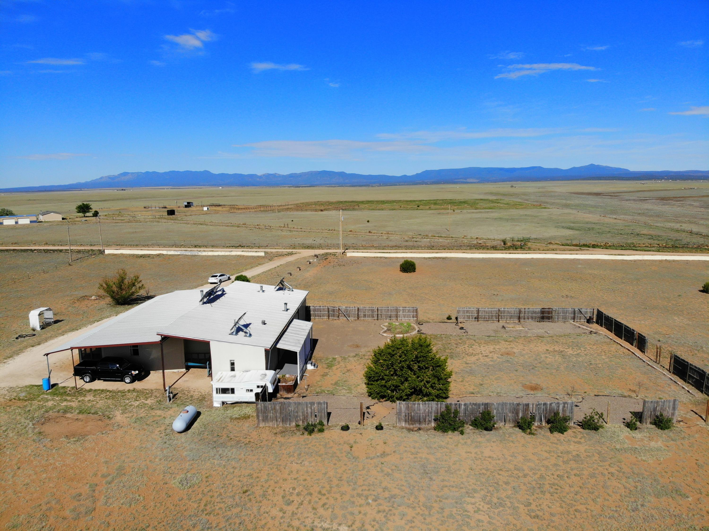 Come enjoy 69+ acres ready for your horses. .Large 60 by 100 ft metal pole barn with 14 stalls and hay storage. Separate shop with power. Large home with 5 bedrooms, 4 full baths, 3 living areas, 2 kitchens. This is two individual manufactured homes that have been enclosed with metal siding to become one structure. Roof is metal. Large carport is attached.