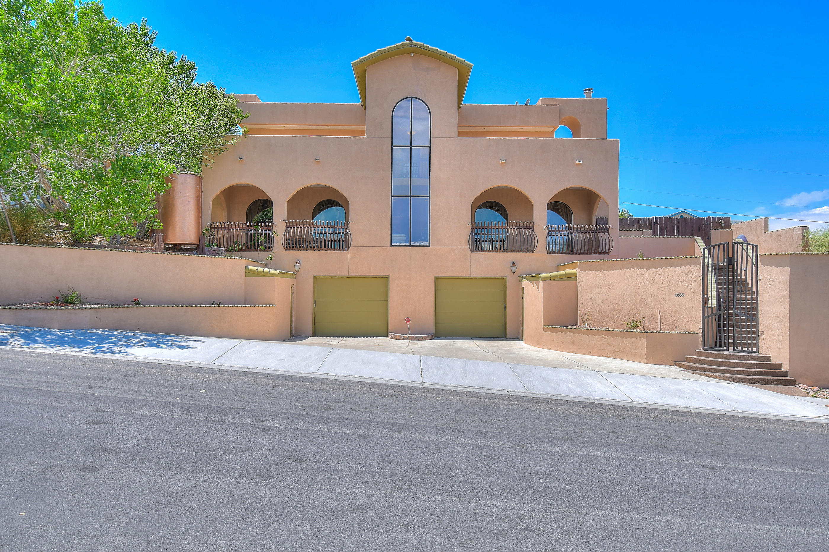 Welcome home to this gorgeous custom Tuscan beauty w/amazing views of the Sandia's! You will be overwhelmed by all of the stunning upgrades. 5 or 6 bedrooms & 3 full baths allows room for large/extended families. Main level bedrooms open to the private patio. Chef's dream kitchen boasts huge gas range, w/griddle and hood. Large pantry, separate wet bar & lots of cabinet space. Sealed brick counter tops on bar/island opens to formal dining space w/fireplace-perfect for entertaining. Spacious bedrooms, large laundry room and two living spaces round out main floor. Upstairs you will find a master retreat w/coffee bar and extra large master bath w/all the features one could ask for. New roof in 2019 & elevator in 2018. Tons of storage. Move in ready. Come and see this unique home today!