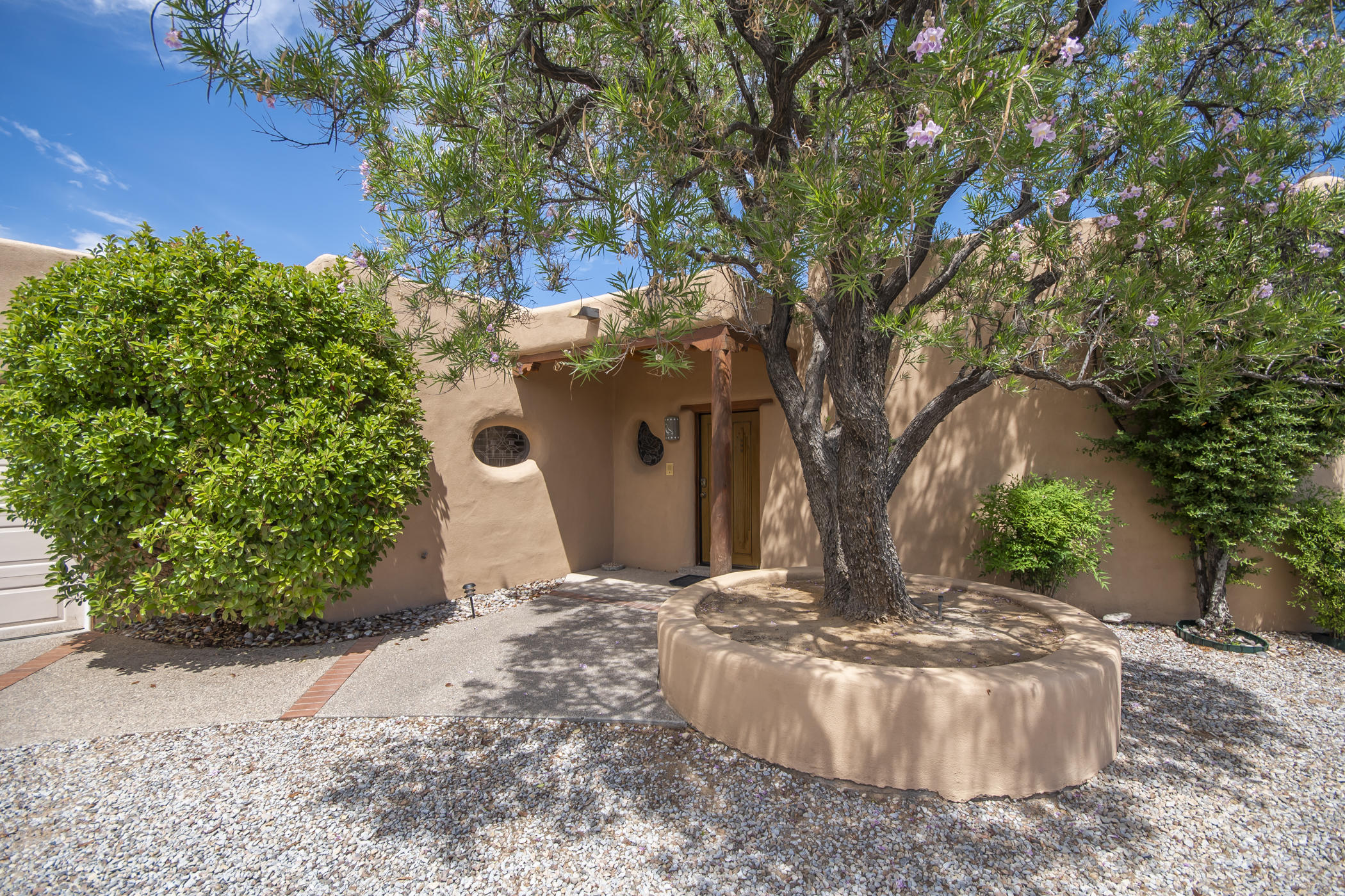 Stunning crescent shaped adobe with panoramic views! Spectacular New Mexico features-Coved, latilla, plank/viga ceilings, hardwood and saltillo floors, three Kiva fireplaces with bancos, custom stained and leaded glass windows, wood casement windows,breakfast nook with built in banco and custom made table, sculpted adobe inside and outside walls. Just wait until you see the Master Bedroom Suite and the living areas with walls of windows looking out to breathtaking views of the Sandias and a sparkling pool iniviting you to take a dip! Adding to the outstanding value are new kitchen appliances, newer TPO roof with a warranty, and a dining room plus office/study with built in cabinetry. Watch the VIRTUAL TOUR! You must experience it to believe it!