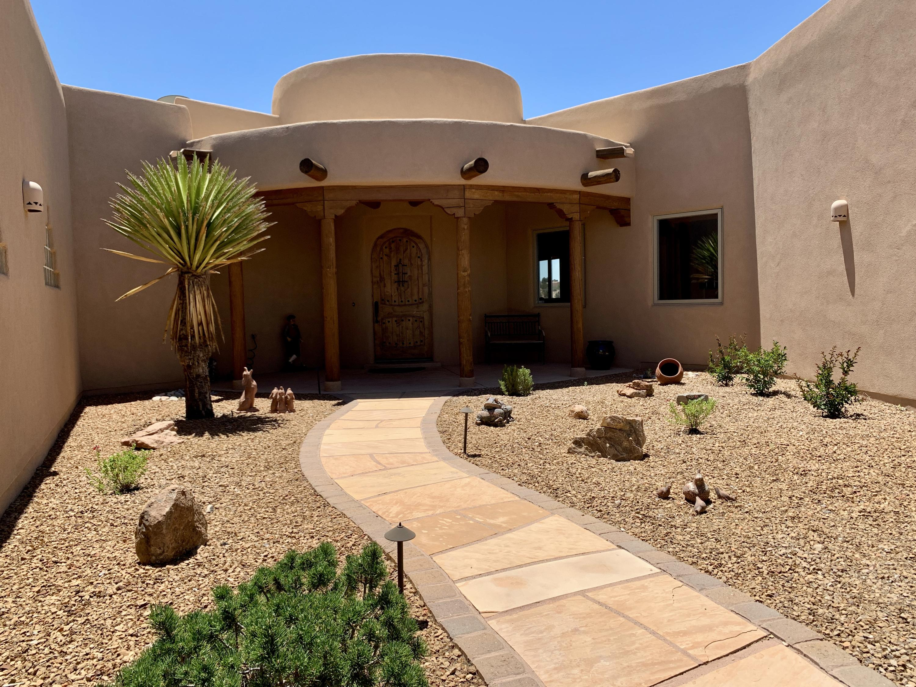 Placitas, just minutes from ABQ and Santa Fe this energy efficient custom pueblo style Kayeman Custom Home is certified at the BGNM Gold level with solar PV and solar thermal installed. Sweeping views atop a ridge in the Anasazi Meadows Subdivision this well maintained home has high end appliances, diamond plaster accents flowing thru a very clean floor plan and outdoor living area. Vigas and latillas in the entry, living and dining areas along with a keva fireplace make a very comfortable and warm entertaining space. Large Master with his/hers closets and stone snail shower. Large 4th Bedroom can be a library or craft room or multi generational room with bed and sitting area. There is attention to detail throughout. Oversized 3 car garage with storage. See Virtual Tour