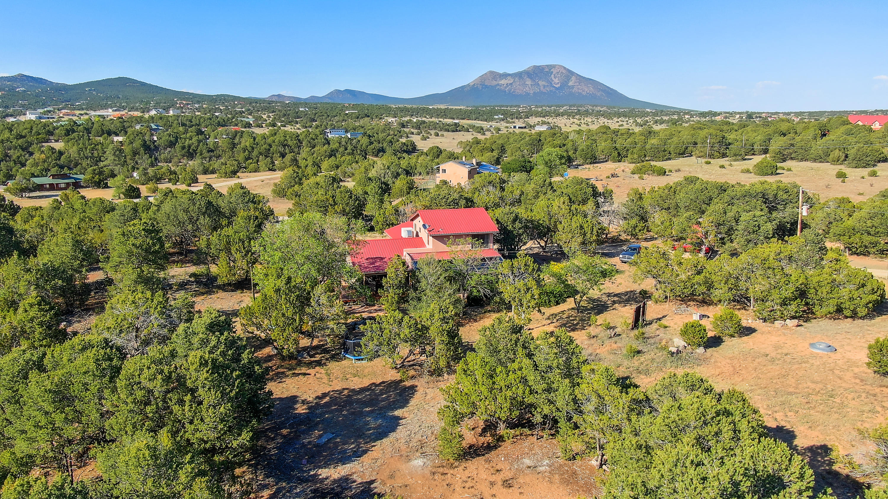 Beautifully updated and upgraded home on over 4 acres in lovely Sandia Park. Spacious great room with cathedral, wood-beam ceilings, laminate wood flooring, and pellet stove. Huge, fully remodeled, gourmet kitchen offers granite countertops, full stainless steel appliance package, breakfast bar, large island, and custom cabinetry. Large heated sunroom with incredible mountain views. Master suite on the main floor boasts 2 walk in closets with organizational shelving, rain shower, and dual sinks. Two additional guest bedrooms upstairs with new carpet and updated full hall bath.  Very secluded, fully fenced, private lot with tons of trees, natural landscaping, remote gate entrance and 2 storage sheds. This is a must-see property! Virtual and Video tours available!