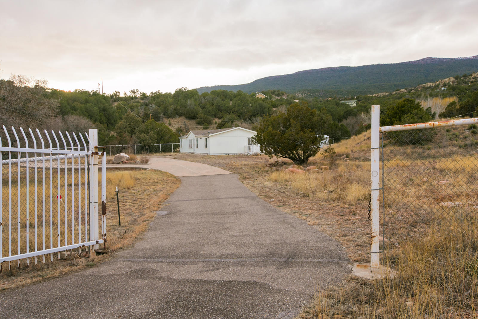 Now is your chance to own a piece of Mountain Tranquility tucked in quiet valley while only 8 min to Albuquerque. LIGHT & AIRY Open Floor-plan with vaulted ceilings and skylights, 2 living areas 2.3 acres with trees and meadow, equipped with irrigation well and CITY WATER. 4BR/2BA maintained home needing a some updates. Formal Liv Area, Spacious Greatrm/Den, Pantry, ample storage, Breakfast Bar/Nook, Utility room with WATER SOFTENER and W/D, Large Master Suite,Garden Tub/Sep Shwr, 4th Add'l Bedrm/Office could be INLAW quarters with separate entrance. New septic, New well equipment, everything is up to code. Inspections complete & ready to go! There is so much potential just waiting for you.