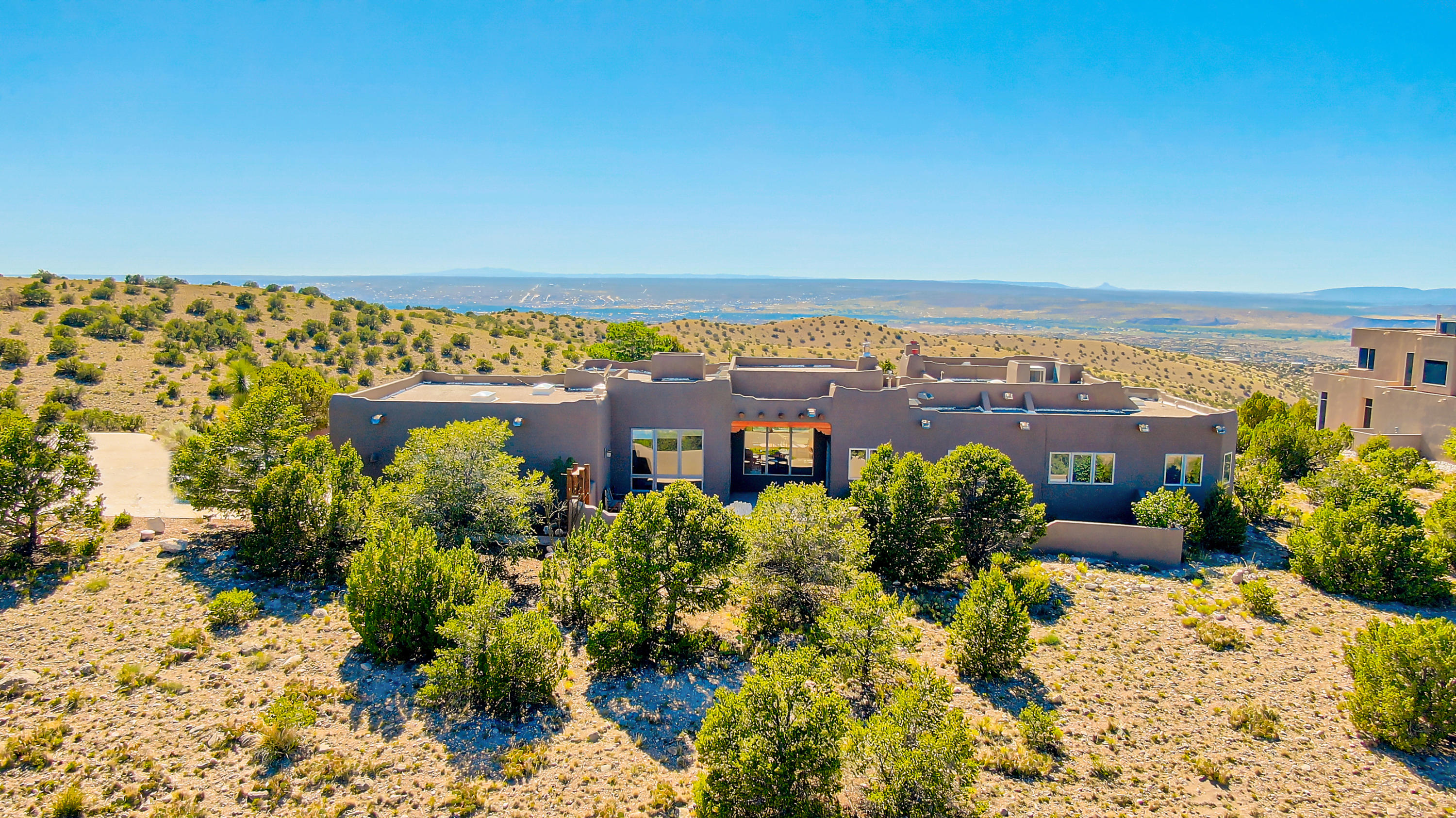 It's all about the VIEWS and New Mexico lifestyle! This much loved home showcases the panoramic vistas of NM and the touches that make it unique. Perched on a ridgetop, saltillo tile floors, split cedar latillas, and vigas, soft plastered walls, & 3 fireplaces exude a warmth rarely found. Updated kitchen with granite counters and gas stove, wine cabinet, and lots of storage plus a lovely breakfast nook.  In addition to the great room, there is a library or tv room with new wood floors. The large master bedroom features a fireplace, french doors to the west patio, and a large window to gaze at the stars. Two generous sized closets and luxurious bath complete this suite. 3 other bedrooms with views just down the hall. Lovely landscaped east and west courtyards with flagstone floors to enjoy!