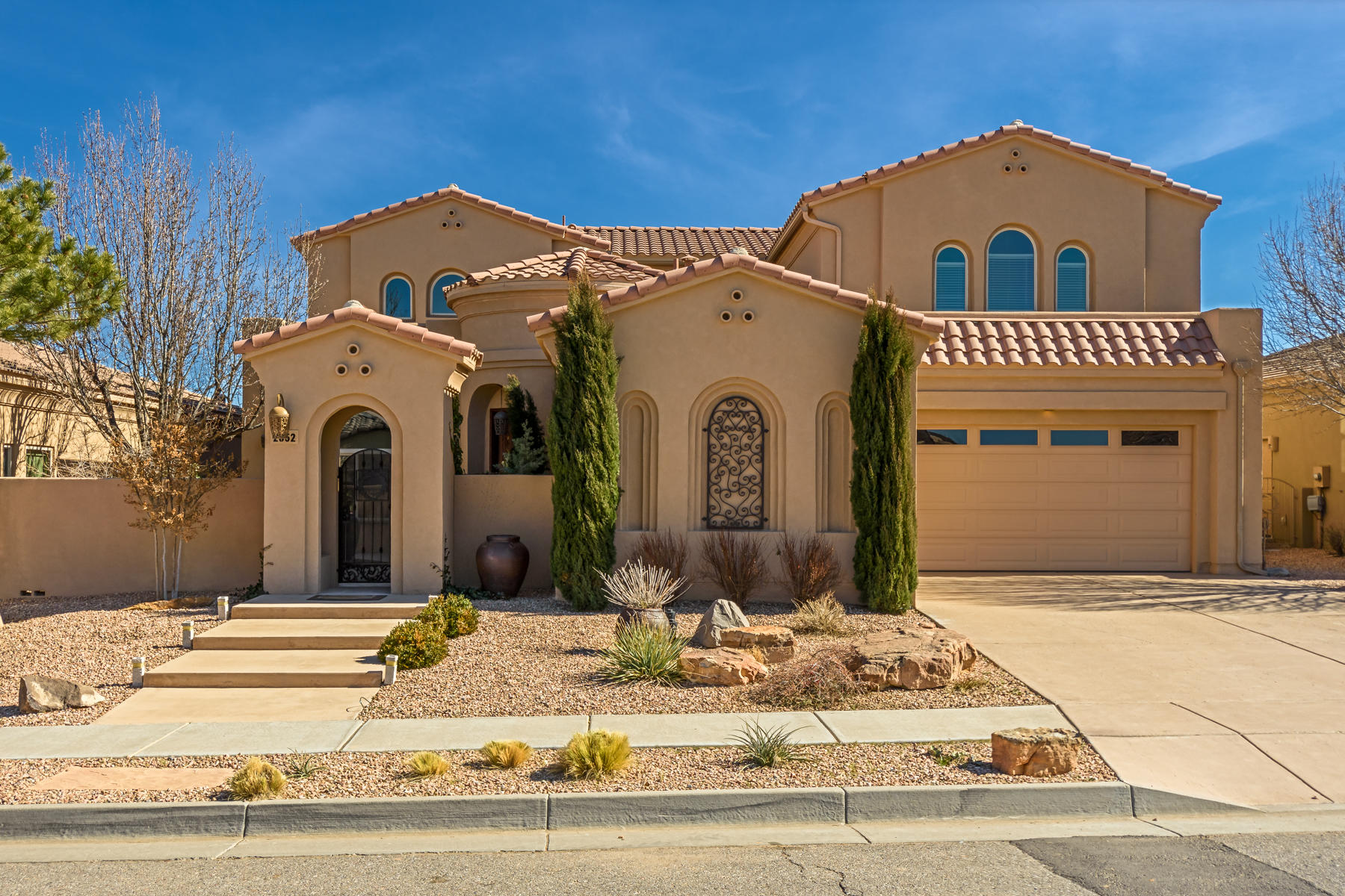 Spectacular former model home in Mariposa with outstanding views of Sandias!  Upscale elegant touches throughout!  Entry features courtyard with a rotunda entrance, spacious kitchen with custom cabinets, solid surface counter tops and upgraded appliances. Breakfast nook open to family room with gas fireplace and formal dining or living area.  Guest suite/office on main level with private bath.  Interior courtyard with fireplace off the office and kitchen.  Large master suite with jetted tub,  separate shower, double sinks, walk-in closets and deck with unobstructed views!  2 additional bedrooms upstairs with Jack & Jill bath.  Trey ceilings, ambient lighting, covered patio, fully landscaped & 3-car garage. Amenities galore!  Community pool and club house, plus playground area and gym.