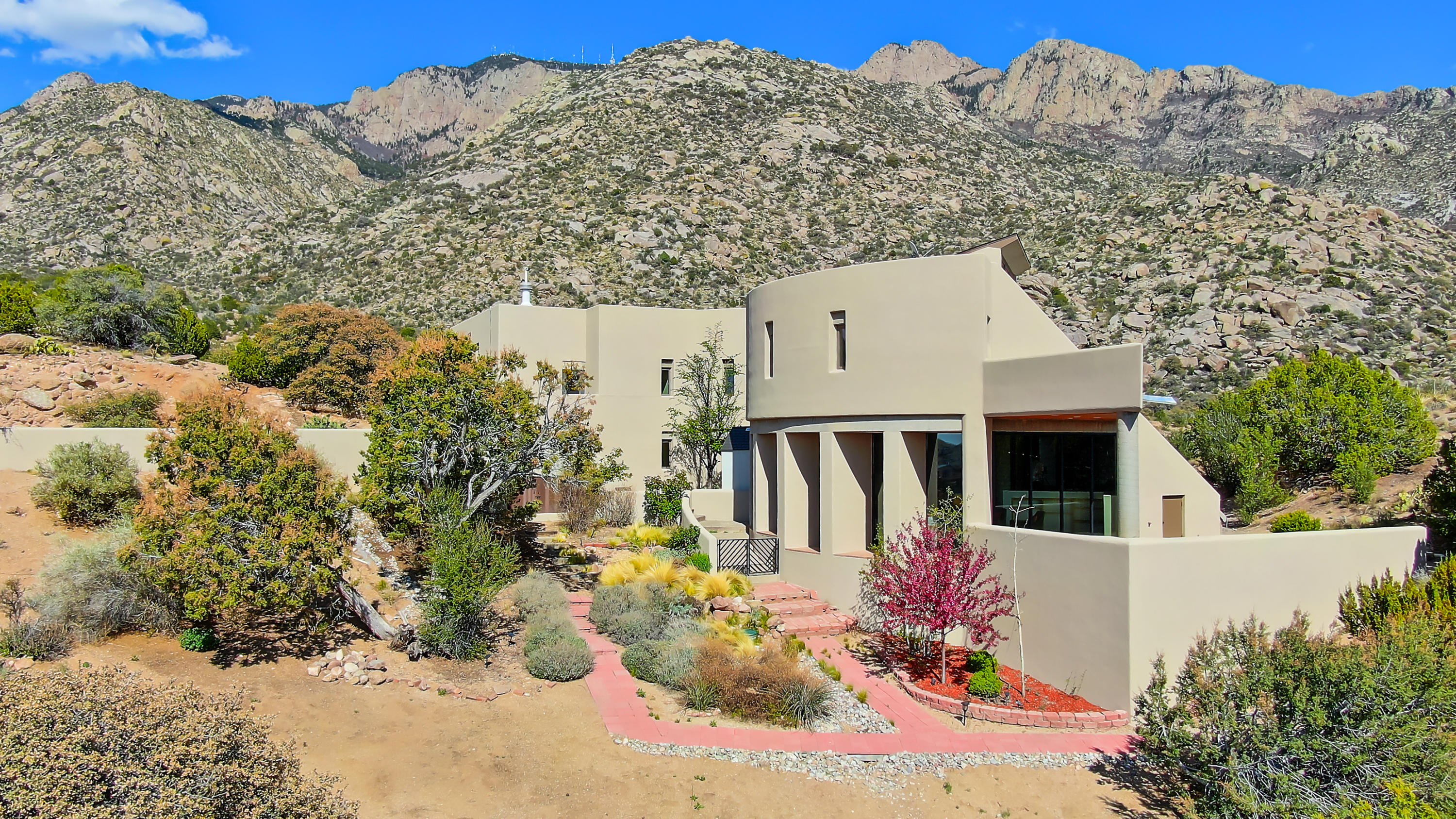Clean, Crisp, Contemporary lines in thisarchitectural masterpiece by renowned Antoine Predock. ''The Boulder House'' represents the finest of Sandia Hts situated on +/-2.2 secluded acres w/awe-inspiring vistas from mtns to cityand up & down the Rio Grande Valley! Walls of windows bring outside in & incredibly showcase the surrounding 360 degrees. Dramatic open living & dining areas provide exceptional flow/function & allows for huge options in use- room for everyone! Two mstr stes, mltple living areas, loft, office, brick & hrdwd flrs & three unique fp's. Tremendous renovations thruout incldng synthetic stucco & septic tank. Chef's kitchen & the master ste will stop you in your tracks! Outside be impressed w/fantastic view balconies, pool w/auto-cover & patios w/more ultimate views!