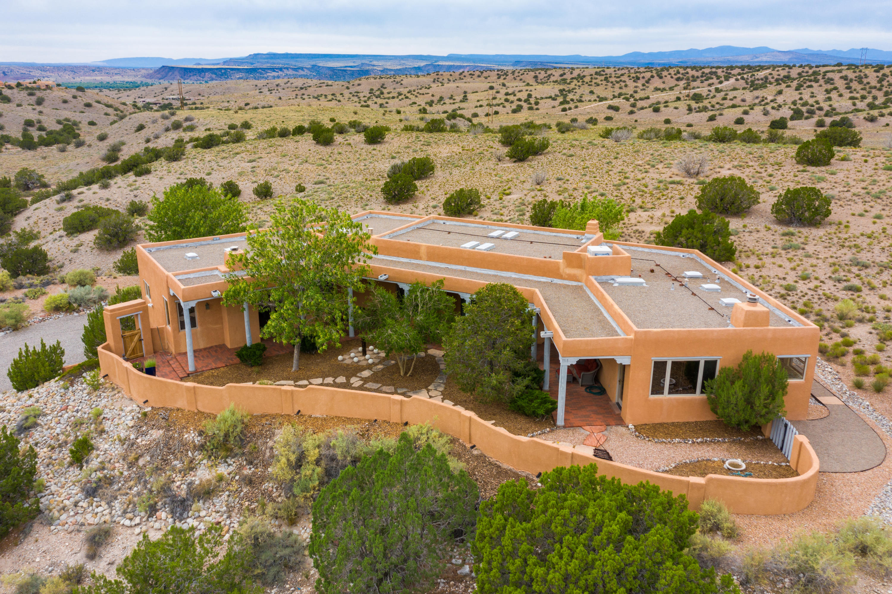 This Southwest custom home is located on a 1.9 acre cul-de-sac view lot in Placitas' La Mesa subdivision. The front of the home features an enclosed courtyard and large covered portal for enjoyment of the expansive Sandia Mountain views! The ''backyard'' is an outdoor enthusiast's dream as the property backs to BLM land with miles of trails. The home's features include beautiful brick flooring, raised, beamed tongue-and-groove ceilings, built-in shelving, nichos and bancos, a custom sideboard in the dining room, 3 fireplaces - both gas log and wood burning with a loglighter and many Pella windows throughout to showcase the amazing views! Please click on MORE for additional information on this amazing property . . .