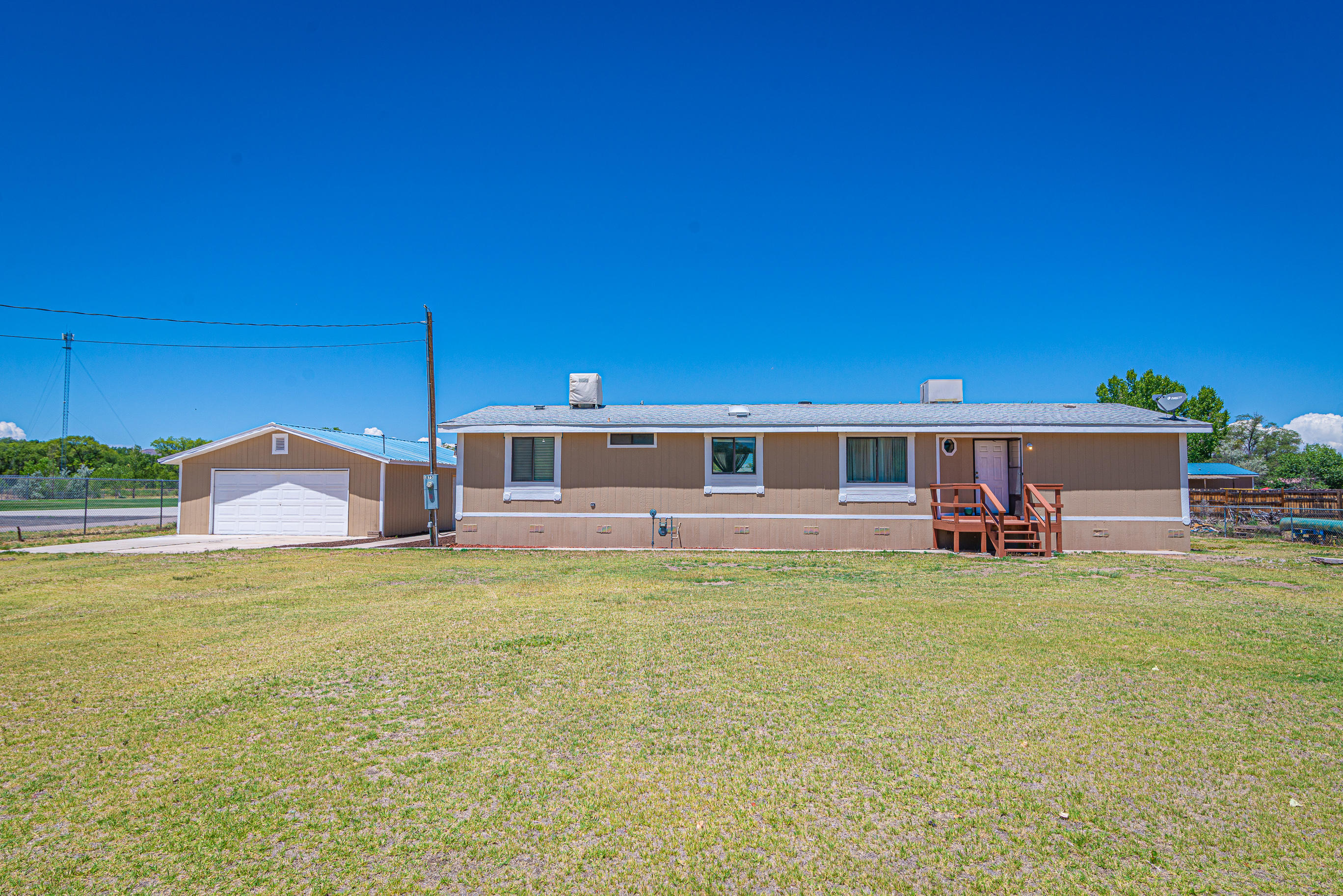Located in the heart of Los Lunas is this well maintained home sitting on half an acre.  Split master bedroom with full bathroom, separate garden tub and shower.  Two way fireplace which can be enjoyed from the living room or dining area. Kitchen is equipped with a cook top, built-in oven, refrigerator and lots of cabinets! Home has  built in cabinetry. Full laundry room and detached two car garage. Located next to the park!