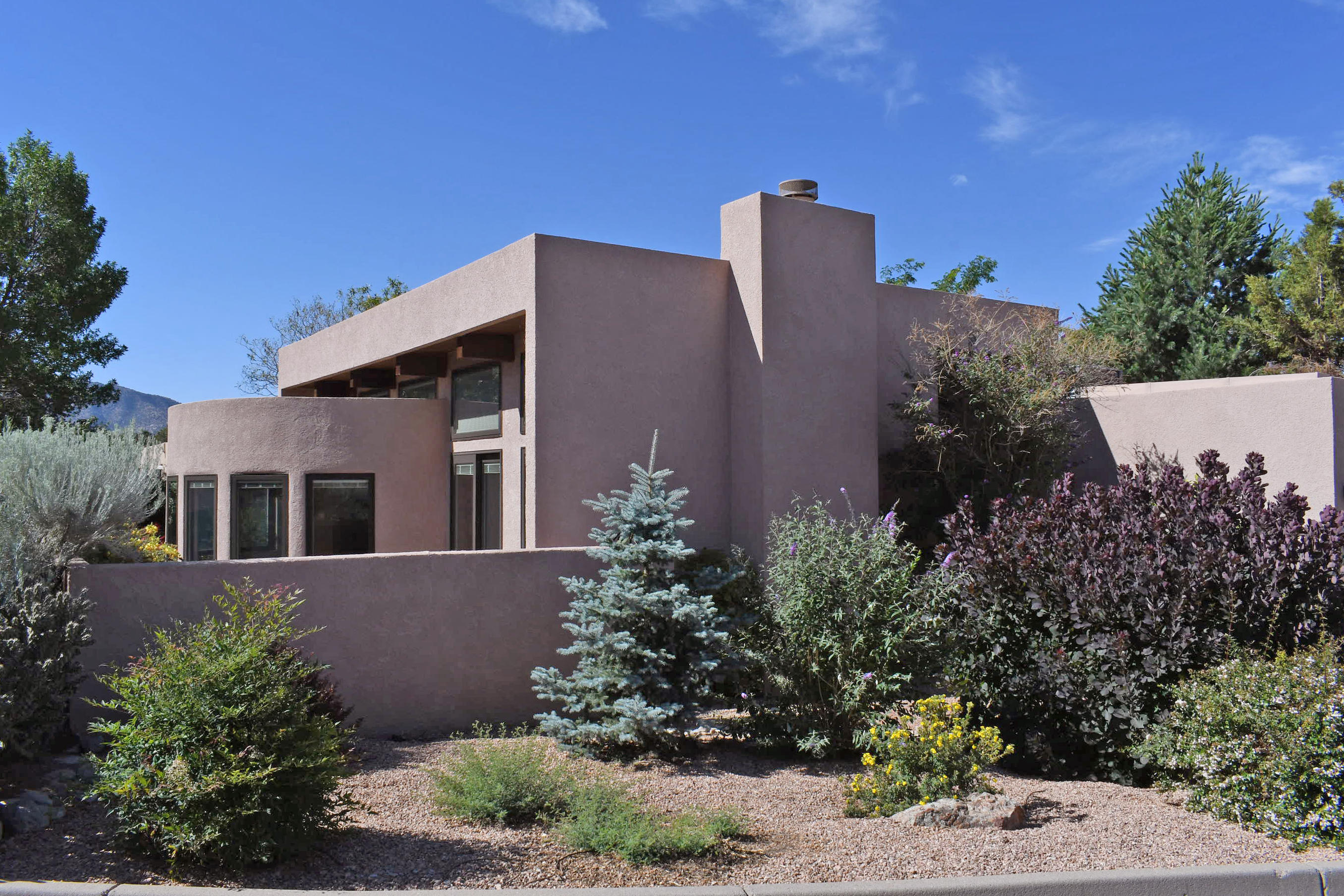 Elegance abounds in this updated, sophisticated Roger Smith jewel nestled at the base of the Sandias.Custom Entry Door.Triple pane low E Pella windows frame stunning views of the Sandias & path of the Tram.New carpet & entry flooring;Granite counter tops through out.Fresh paint;CA closet shelving w/shoe cubbies;Lg MBR closet includes 'hidden' closet for expansion. Charming Sunroom could be office, workout, hobby, studio, or at-home schooling room.Fully irrigated landscaping w/raised garden beds, seasonal blooms & patios surround the exterior. Finished 3 car heated & cooled garage. 7.2 KW wholly owned solar elecric & other systems provide unparalleled comfort, control & economy (ask about Net Metering) A FABULOUS MUST SEE TODAY!!
