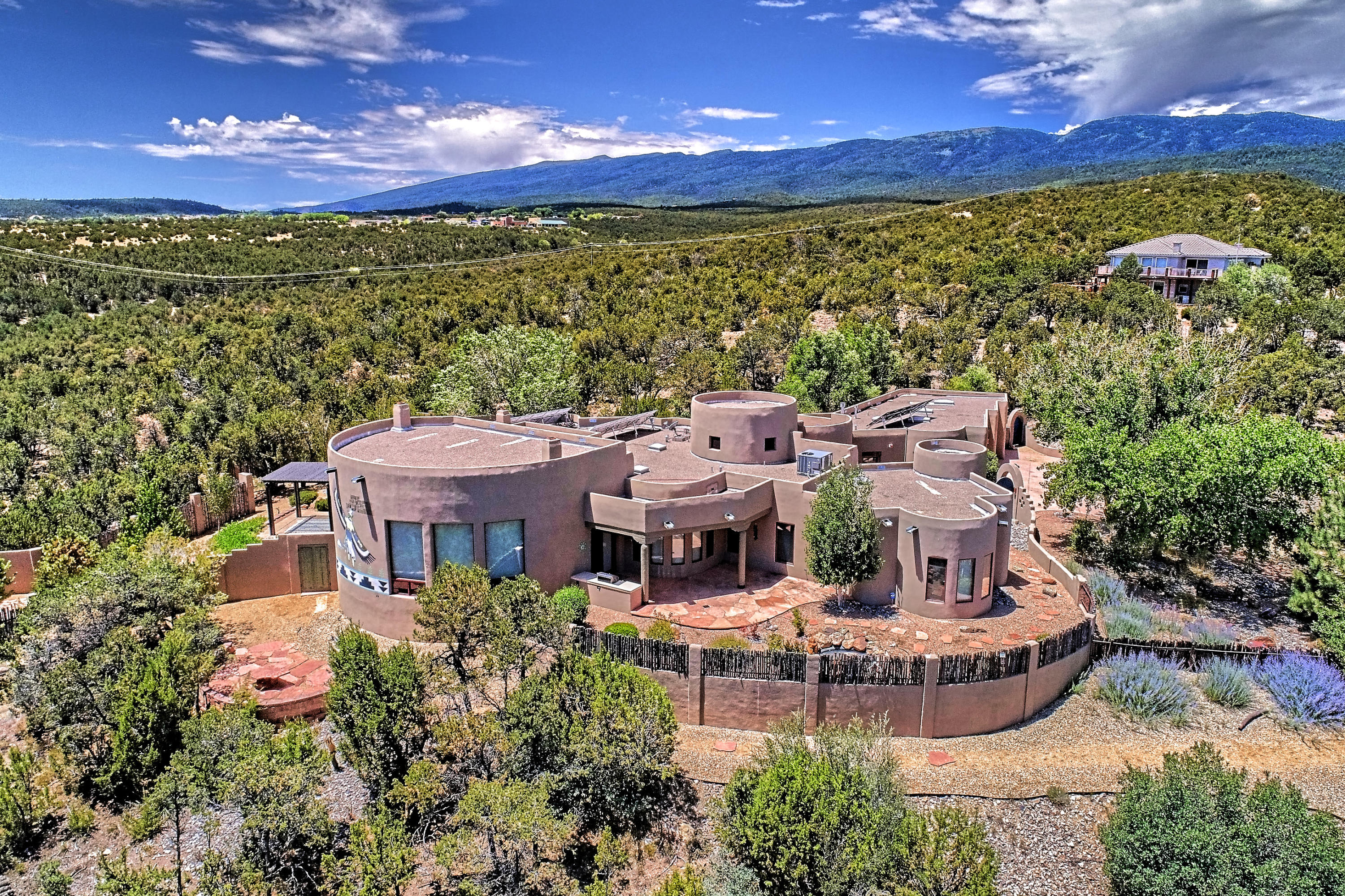 Stunning Southwest Pueblo home in beautiful Paa-ko. Nestled in the trees and situated on 3 acres with amazing views of the Ortiz and Sangre de Critso mountains! Attention to detail abounds in this 4 bedroom, 5 bath, 4514 Sq Ft home, featuring; 2 living areas, formal dining, gourmet kitchen with breakfast nook, 3 Kiva fireplaces, nichos, adobe accents thru-out, security system, and a 4 car oversized garage with a 1 car detached garage that is perfect for workshop or studio. Several outdoor living spaces offer the perfect setting for entertaining or relaxing on one of the many patios and sitting areas, with amazing views and a beautiful water feature! Must see to truly appreciate this stunning home!