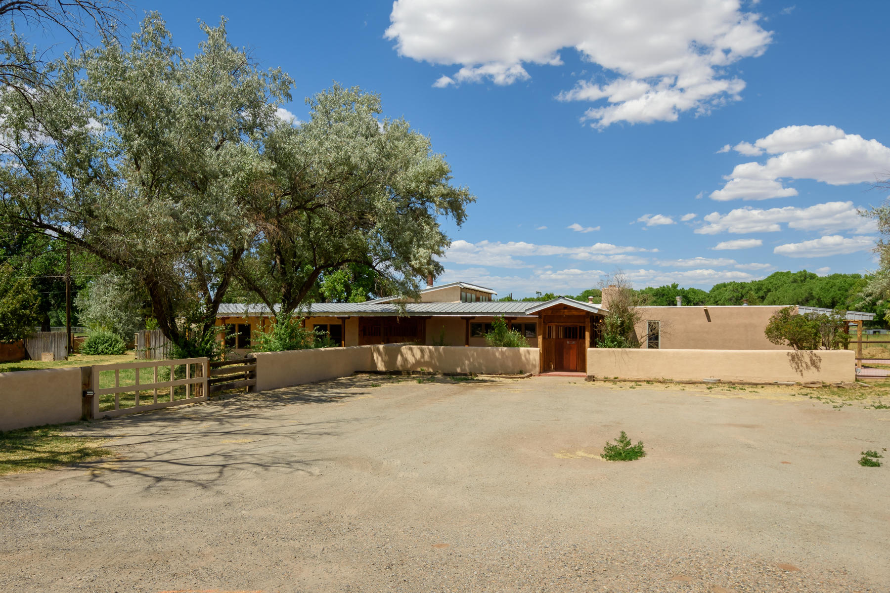 Welcome home to your new, beautiful Los Lunas hacienda on 3 acres. This home has so much to offer, beginning with the classic and subtle Southwestern touches like beamed ceilings, kiva fireplaces, and brick floors. Huge living room is flooded with natural light and leads to the kitchen/dining room combo, which lends itself to easy entertaining. Sun room is massive and can have so many uses. Master Bedroom wing includes a sitting area and an all custom tile bath and double closets. Office/bonus room can be used as a wonderful space to work, hobby or another bedroom and has its own cozy kiva. All of this, AND a 742sqft apartment perfect inlaws, older kids, guests. Horse stalls, storage, carports, and so much space! You are going to love it here!