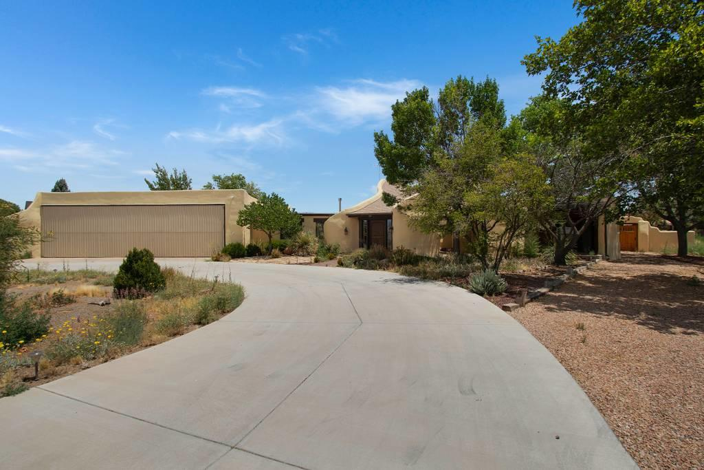 OPEN HOUSE Sunday, 8/2 1-3p. The Sky is the Limit! This is your chance to own a stunning southwestern adobe style home.  You will be amazed by the splendor of the kiva style great room from brick floors to  the sky high ceilings!  The owner's suite is separate from the other bedrooms and has a beautiful en suite bath with separate jetted tub and shower.  This bedroom has 2 cozy patios for extra outdoor enjoyment.  The kitchen is modern with a butlers pantry and large island.  There is a separate living area with a quaint sunny window seat perfect for relaxing.  This home flows to the outdoors with numerous patios. The yard has been well landscaped and separated into two large garden like spaces.  All of this is located in the Los Lunas Mid Valley Airpark with your own airplane hangar.