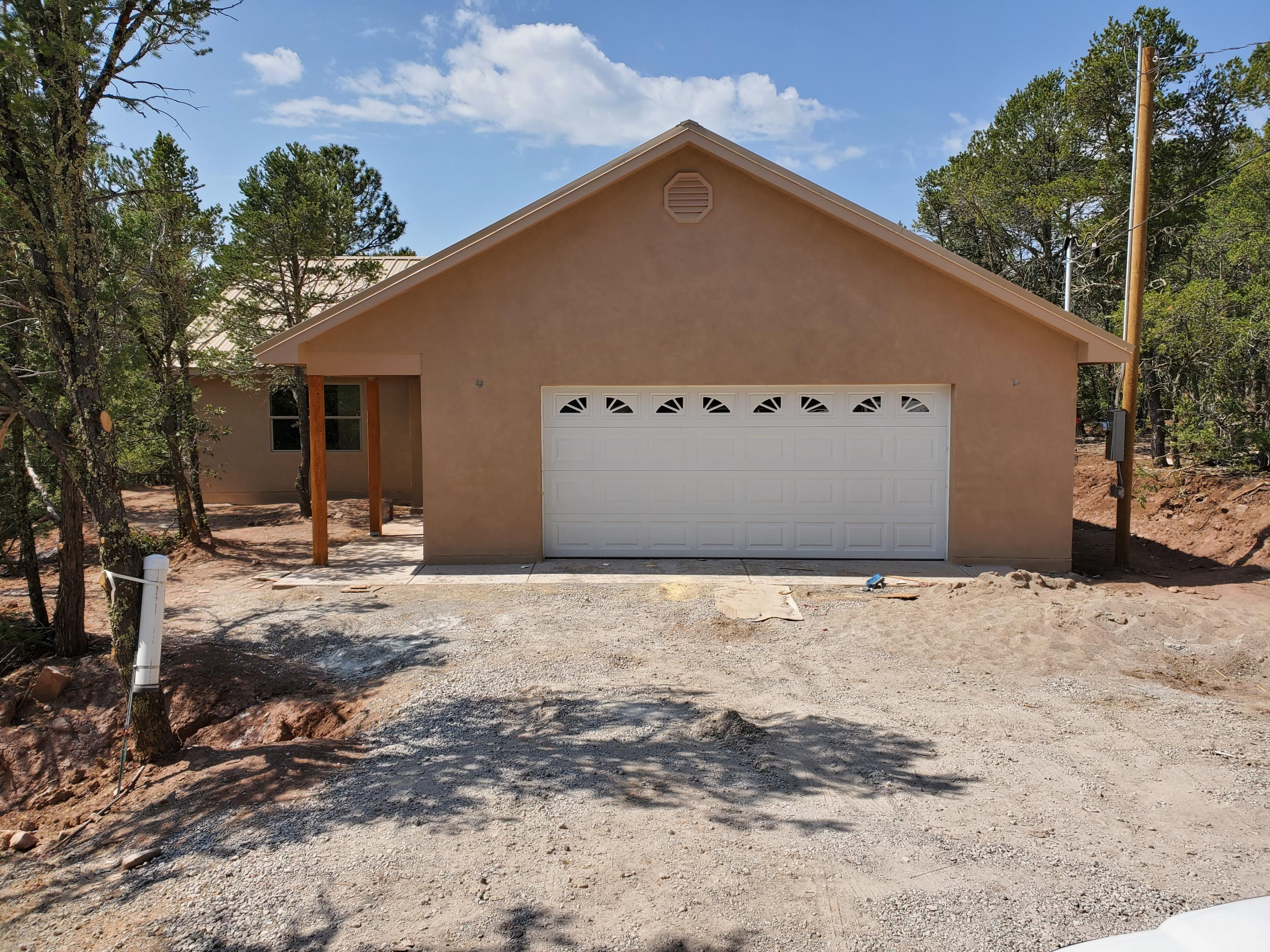 Under construction! A nice home with 1,551 sq. ft., 2 bath, 2 car garage nestled on a gorgeous lot with trees, trees and trees!  Located in a small gated compound with only 2 other neighbors.  Kitchen has eat at bar, granite countertops and microwave over stove. Private well, metal roof, pellet fireplace, central heat, refrigerated cooling, covered patio, skylights. Master has dual sinks, shower and a walk in closet.