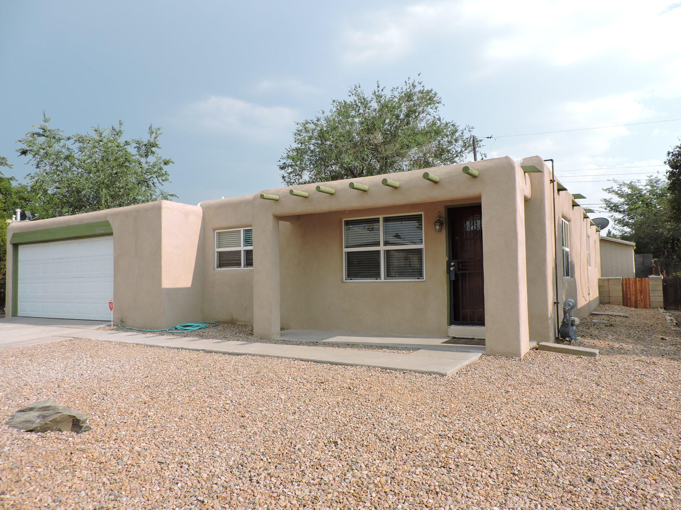 Cute NM style home, in a quaint neighborhood.  Nearby elementary school and many other amenities.  TPO Roof installed 2018, warranty transferable, completely re stuccoed July 2020.   Bathrooms remodeled, tile and hardwood floors throughout, no carpet! Kitchen and dining open area perfect for entertaining.  Updated Pella vinyl windows, new kitchen counter tops.  Garage is oversized with extra storage space above, Back yard is large and has potential for many landscaping options.  Storage shed in backyard equipped with electricity. Baseboards being installed and floor finishes coming! Don't miss this opportunity for a great home looking for new ownership! Offer Now!