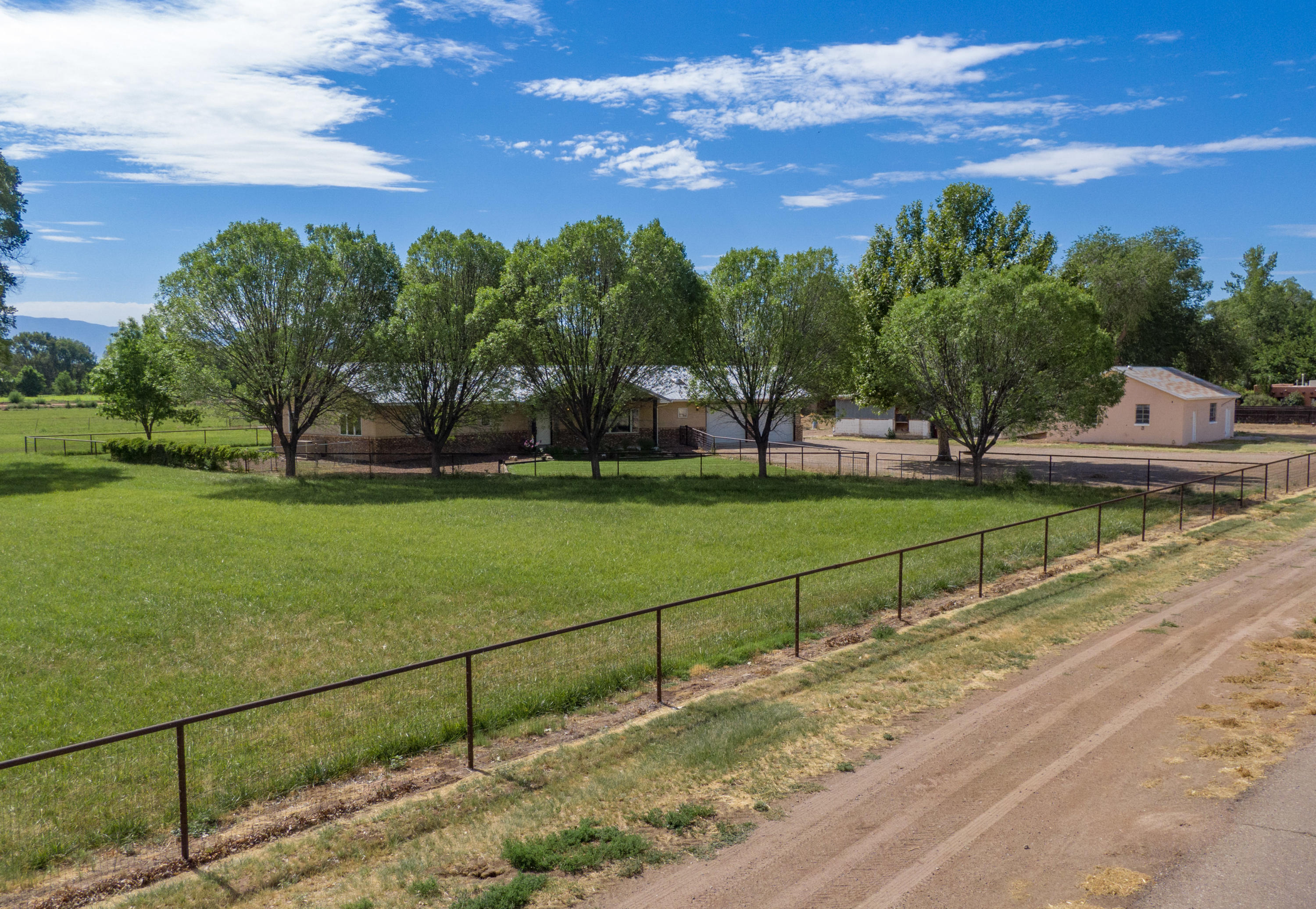 This beautiful custom built home in the heart of Bosque Farms is a farmers dream! On 8.22 acres this 2463 sqft home consists of 4 bedrooms and 2.5 bathrooms. The open concept floor plan, over-sized dining room, and living room w/ vaulted beamed ceilings and cozy fireplace is perfect for entertaining. Take the fun outdoors w/ a large covered porch overlooking the swimming pool and great views of the pasture and Mountains. Cross fencing separates the back yard from the field which is planted w/ approx. 5 acres of pasture + plenty more space perfect to expand the pasture or add horse stalls and/or an arena. Approx 920 sqft work shop, large storage building all w/ power, and 3 phase available if needed, additional hay storage, stock tank., irrigation +2 wells.  Must See!