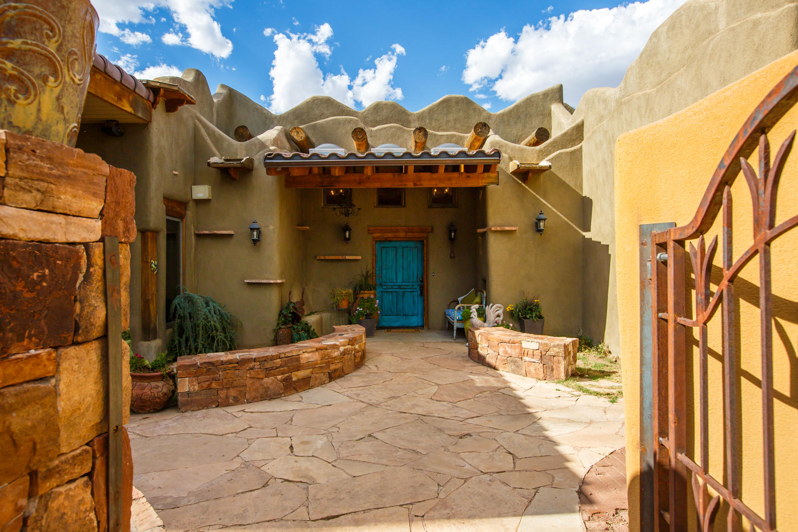 In the North Valley's Los Ranchos de Albuquerque, on a full acre of irrigated land along Rio Grande Blvd, this custom, one-of-a kind home and its guardian lizard await you. Walk through the partially covered courtyard, and upon entry to the home you get a sense of spaciousness, whimsy, and Southwest artistry, in high beam Viga and Latilla ceilings, exposed adobe and diamond plaster walls, artistic mosaics, and stone floor. Multiple living spaces, indoor and out, make it easy for generations to live together. The loft wing has a separate entrance with a bedroom, bath, living space, and room to add a kitchenette. This adobe home is efficient, with radiant in floor heat, and refrigerated air to complement passive nighttime cooling. Garage workshop with a half bath and rooftop deck caps it off