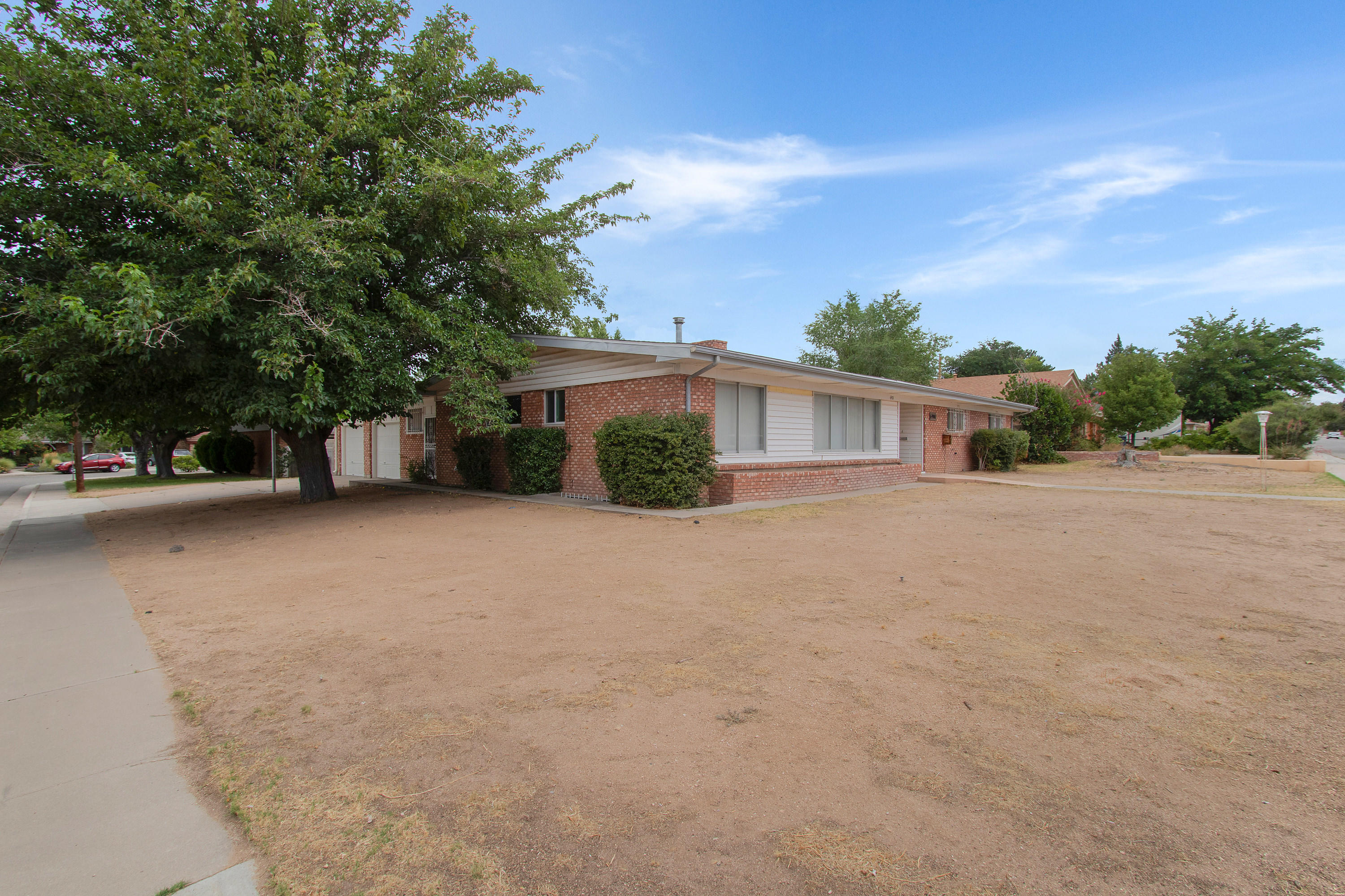 This spacious Mock Home is located on a large corner lot and features 4 large bedrooms, 2 1/2  bathrooms plus a feature unique in Albuquerque homes- a finished basement, an ideal place for a game room, TV room or teen (or adult) hangout. In addition to the family room and living room/dining room combo a breezeway between the garage and home was converted into another large living space. Use as an exercise room, office, hobby room, the possibilities are endless. The oversized garage has a nice workshop area. Energy efficient Champion windows throughout the home. Midtown location in a beautiful established neighborhood minutes to Uptown and freeways.  The great floor plan is waiting for new owners to put their personal touches on it. Schedule your home tour now.