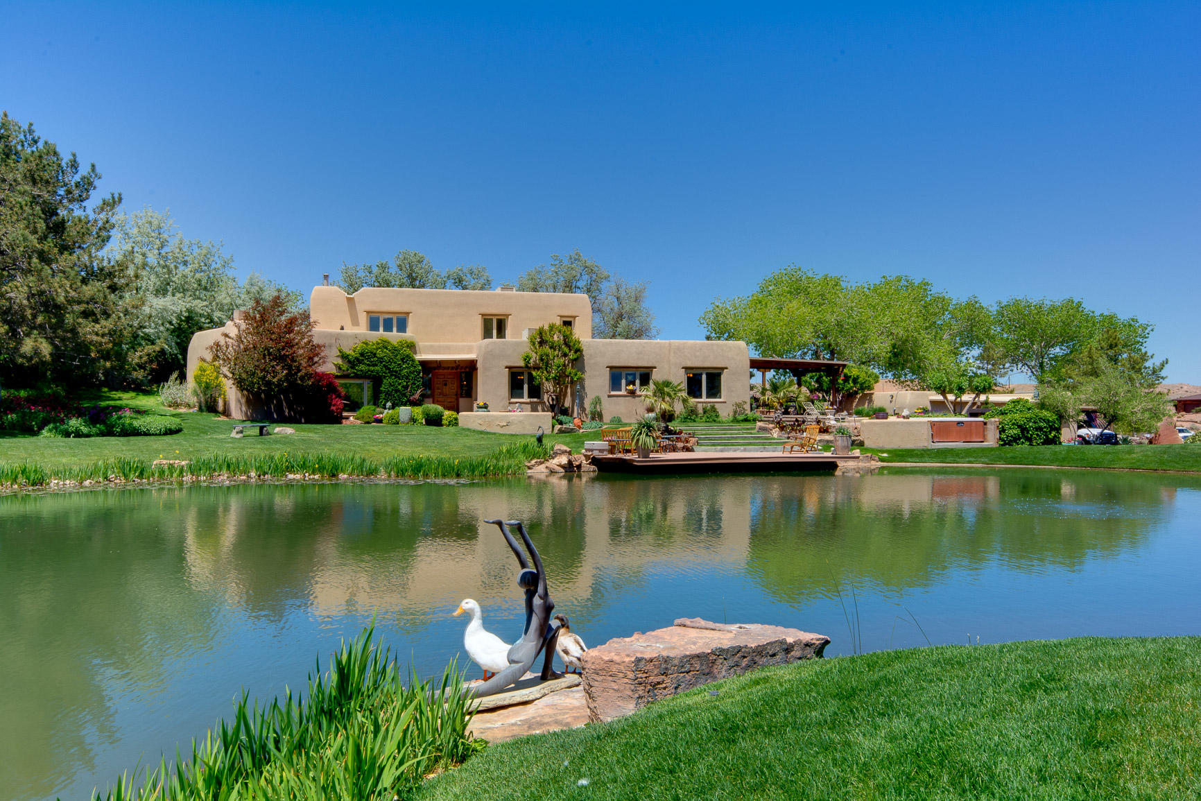 Extraordinary Nat Kaplan Adobe home nestled on a master designed private oasis in the desert w/impeccable craftsmanship, understated elegance & timeless finishes/amenities; Spanish Boveda entry, T&G beamed ceilings, sandstone floors, 2 fireplaces, radiant heat, outdoor kitchen, fire pit, hot tub & studio. Country lifestyle on a secluded 13.3 acres (4 parcels/city water for house) opulent grounds & breathtaking mountain views; a canopy of gorgeous cottonwoods, grassy hills, 80 tree orchard, gardens, expansive pond & waterfall, go swimming or fishing, it's an ecosystem w/bass, bluegill, bull frogs, baby fish nursery cove, ducks, water lilies & energized by windmills that constantly refresh the pond from the well w/pre-1907 water rights! Visualizing a vineyard? This could be your Dream Home!