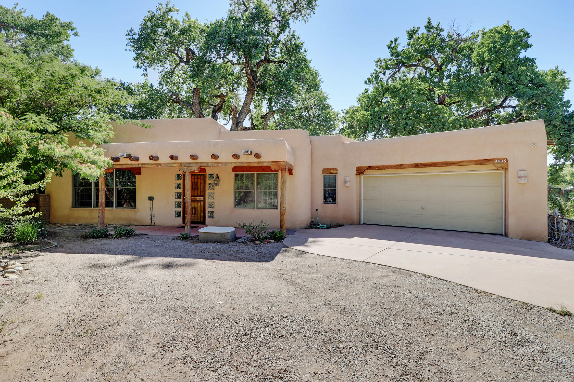 Tucked away next to an Acequeia is this beautiful home surrounded by trees. This custom home is a tranquil lush oasis from the busy city. Drivey down the long drive away from the street and feel your worries fade away! Custom home on .26 irrigated acre with all sorts of fruit trees and Cottonwoods giving shade. Inside find vigas and corbels, Tongue & Groove ceilings, tile floors, Nichos, a Kiva Fireplace for those cozy winter evenings! large well-designed kitchen with sunny breakfast nook, and formal dining area.  Gas Stove, microwave, refrigerator stays. the master is very spacious with a spa-like bath! Two more spacious bedrooms, one would make an excellent office. This well-cared for home is ready for you. On demand hot water, and pella sliding glass doors go outside to paradise!