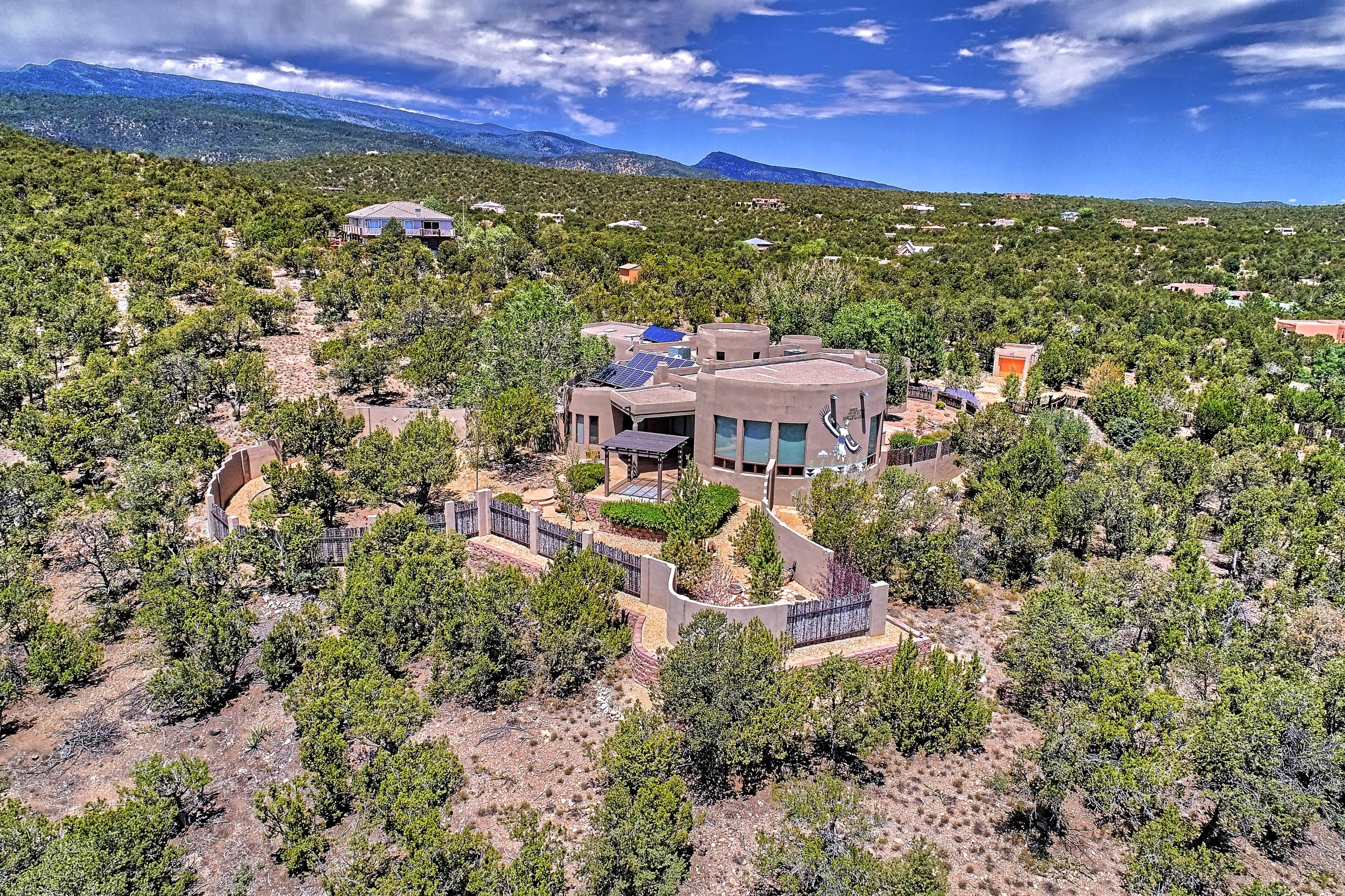 EXCEPTIONAL Home in Paa-ko, perfectly positioned to take advantage of the dramatic views of the Ortiz and Sangre de Cristo Mountains! Beautifully landscaped & inviting courtyard lures you inside to the grand foyer w/ soaring viga spoked ceiling, arched entry's, & tile mosaic. Chef's Kitchen features a 6-burner WOLF range, Sub-zero fridge, & double-ovens. Spacious great room with 2 living spaces, spectacular views from the floor to ceiling windows and wagon wheel spoked ceiling, 3 kivas, nichos, adobe accents, hand-painted light fixtures.. Amazing outdoor living spaces offer the perfect setting for entertaining or star gazing on one of the many patios and sitting areas, with outdoor kitchen, patio for hot tub, amazing views and a beautiful water feature! Must see to truly appreciate!