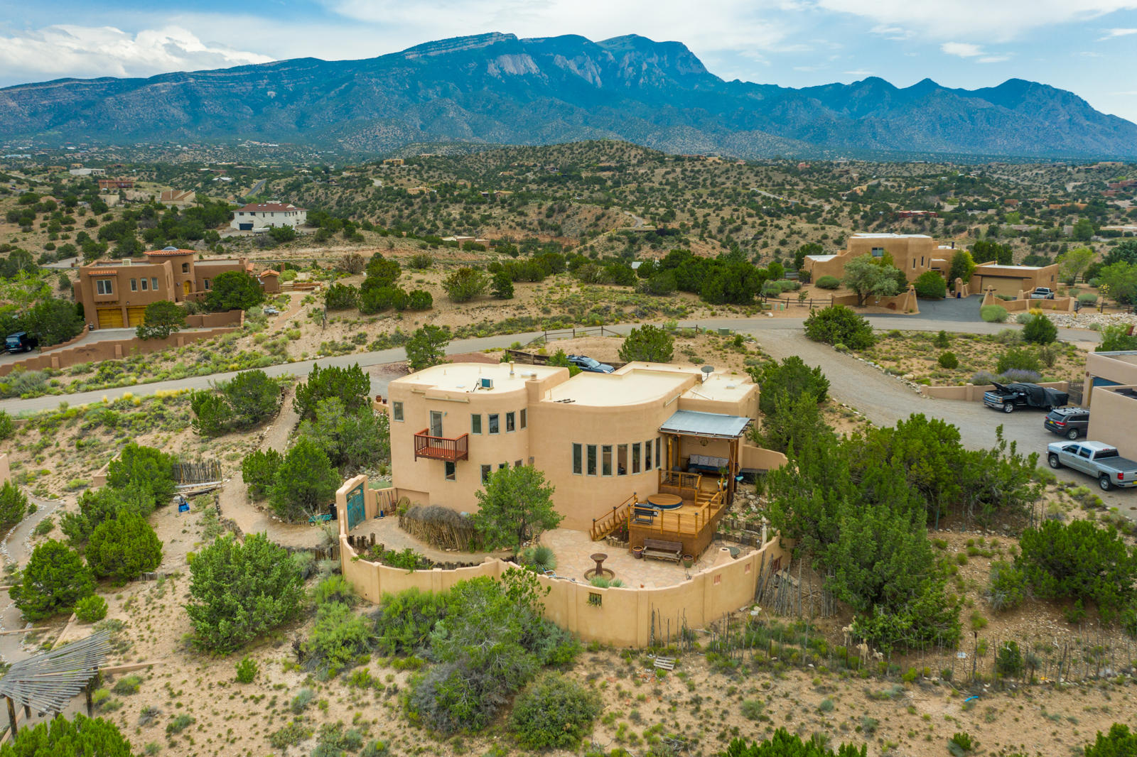 Amazing views of the mesa's capturing the extraordinary blues and purples changing with the light. This beautifully updated home features  a flowing open design with wood and tile floors. The soaring ceilings reflect the southwest architecture wood and beamed ceilings and a charming kiva fireplace with banco's. The newly renovated kitchen has stainless appliances, granite counters and island. A large eating space overlooks the living room and beyond to the views. The large, private primary suite is upstairs offering complete privacy, walk in closet, full bath with separate shower, a reading nook and balcony.  The two guest suites are tucked away downstairs with a Jack and Jill bath. Plenty of out door space with a multi-level deck, separate dog run and parking for the RV.  New TPO Roof