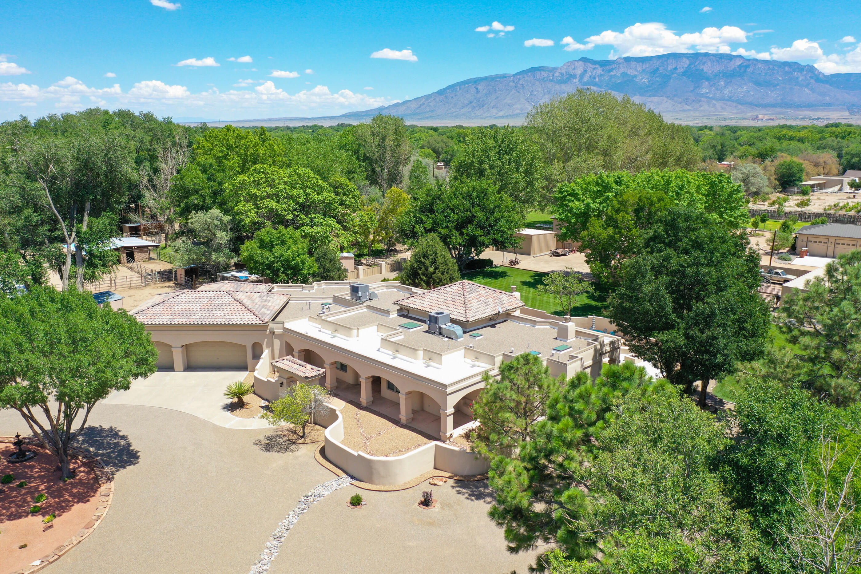 Welcome to this stunning property located at the South end of Corrales, offered by the original owners.  Situated on over an acre, you'll want to spend time enjoying the lush green outdoors and mountain views.  Wonderful floor plan featuring a large great room with high ceilings accented by beautiful vigas on tongue & groove wood slats.  Large kitchen with great storage and a formal dining space.  Beautiful horse facilities with 3 stalls, tack room & riding arena both with lighting, and a horse wash area too.  Just minutes to the Bosque Trail.  Pride of ownership throughout including high quality & timeless finishes.  New synthetic stucco and new roof recently installed, this property has been impeccably maintained. Irrigation through MRGCD.