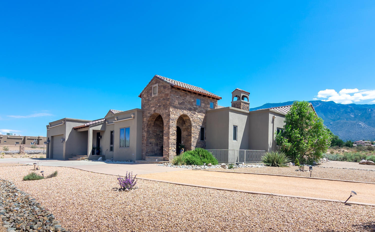 AMAZING custom home beautifully located in North Albuquerque Acres, situated on .89 acre lot with gated entry & commanding VIEWS of the Sandia mountains! Step inside & experience incredible architectural detail, with exceptional finishes: stone accents, arched doorways, crown molding, custom cabinetry & built-ins, top of the line lighting, wood windows & handsome wood floors. Gourmet kitchen with Wolf appliances, subzero, granite, & breakfast bar island! Exquisite formal dining room, & family room with gas log fireplace! Separated master retreat offers patio access & luxurious bathroom!  Expansive walk-out basement includes: a bedroom, study, hobby room, full bathroom & access to patio & backyard! Spacious backyard with covered and open patios, fireplace, turf & splendid Mountain VIEWS!