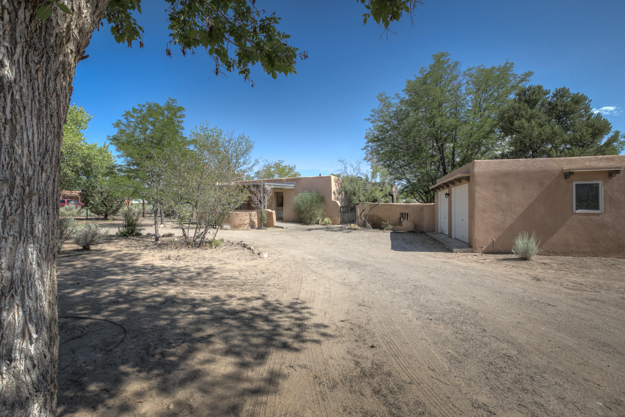 You just have to check out this charming Adobe/Pueblo home with  handcrafted moldings and hand-carved doors.100 % Solar energy, panels are owned by seller, 2 wells 1 private and 1 irrigation. There is also a detached Casita/Studio with a 3/4 bath. 2 separate garages with carport space as well. Check out the adobe playhouse and kiva doghouse built into the courtyard wall!! This one of a kind home is nicely situated on an acre.The well, septic and home Inspections have been completed recently.  Both the well and septic inspections passed and the repairs called out on the home inspections are nearly completed.  If buyer wants any inspections it will be at their expense