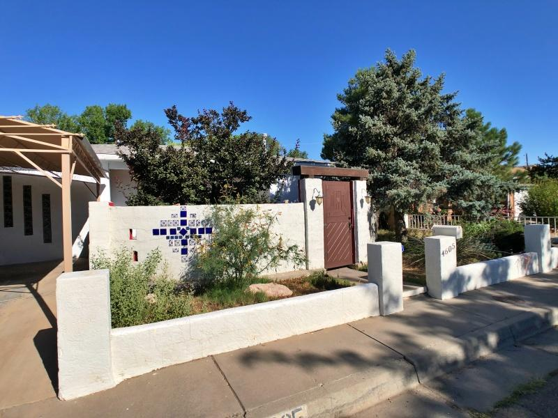 Open House Sunday 2:30-4:30p. See the 3-D Tour! Sweet & spacious North Valley adobe home on quiet cul-de-sac in historic Los Griegos Neighborhood. Enter into private, lush front courtyard, with shaded east-facing porch. Inside, there's much to love: living room features dramatic stone fireplace & marvelous arched entry leading to 2nd living area. The large & gracious formal dining room + open kitchen floorplan create seamless flow between areas--perfect for large gatherings or intimate affairs. Primary Bedroom has HUGE walk-in & laundry room. Hardwood floors & T&G ceilings in several rooms + cool barn door sliders adorn both bathrooms. Relax under the shaded back patio, surrounded by mature trees & wonderful landscaped greenspace. Adjacent to Griegos Lateral Bike & Nature Trail--Come see!