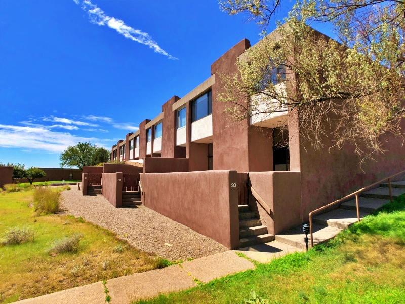 See the 3-D Virtual Tour! Sitting on 40 acres along the Rio Grande Bosque, La Luz del Oeste is rather unique. Welcome to 20 Berm NW! All adobe construction, this townhome sits on the edge of the compound, with commanding MetroABQ skyline & magnificent Sandia Mountain views. High-walled, the shaded west courtyard is lush & private, with fruit trees including pomegranate & fig. The east courtyard opens to 5 acres of greenspace & gardens that surrounds the community. Inside, the kitchen is fabulous: New granite, stainless, pantry, b'fast bar, sweet glass-&-ceramic tile backsplash & original refinished cabinets. The front office has sliding plantation shutters, courtyard access & 1/2 bath en suite. Large upstairs Primary has 1-of-2 Kivas & stunning views. Fall in love with your home--come see!