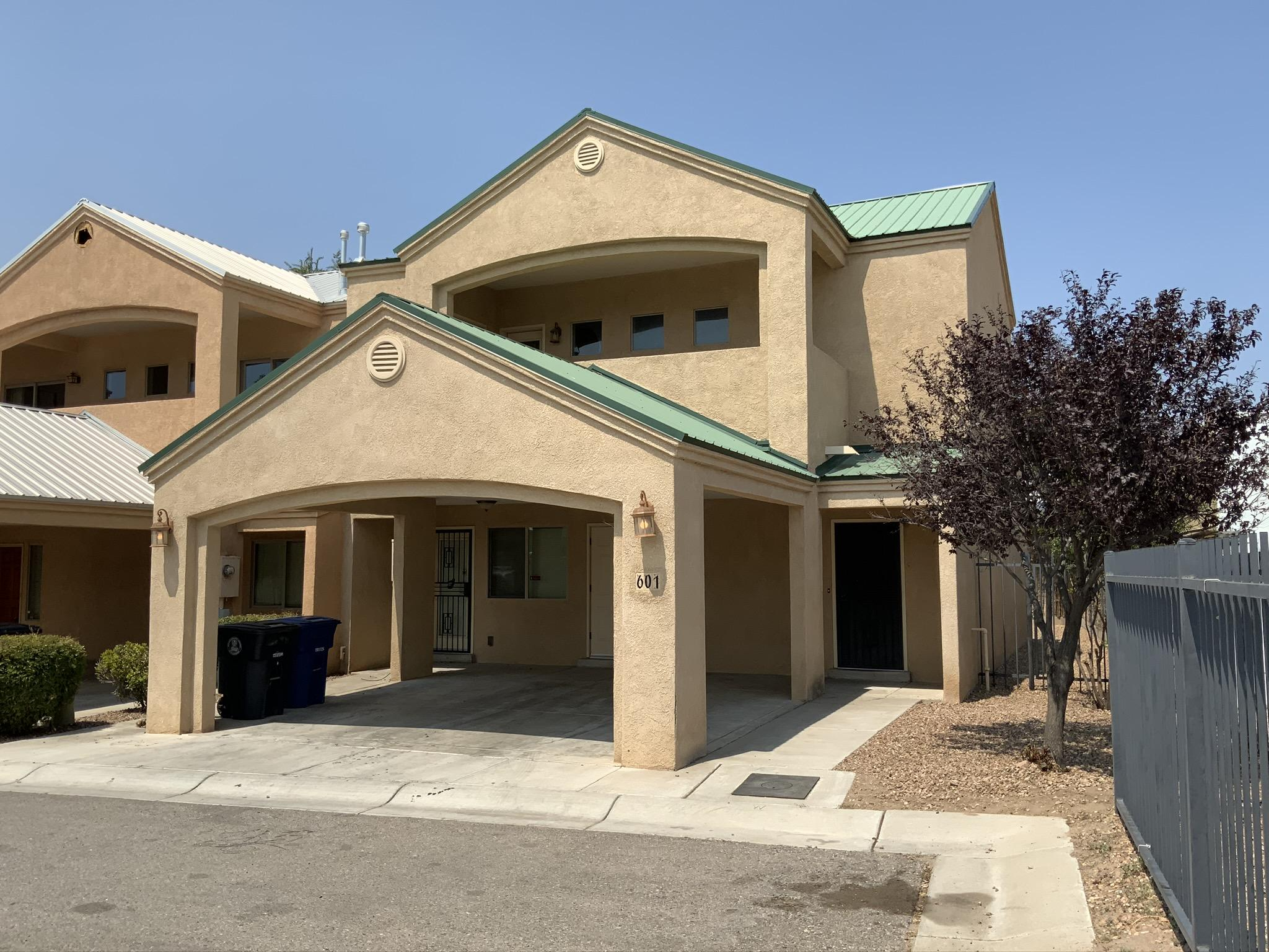 Custom town home near Barelas coffee house and Indian Cultural Center! This upgraded and custom built town home features a metal roof, 2 car carport, storage closets, granite counters, new carpet, refrigerated air, custom solid wood doors, private sinks in each bedroom, large walk out patio with views and a private yard fenced with custom coyote wood planks. Priced to sell quickly.