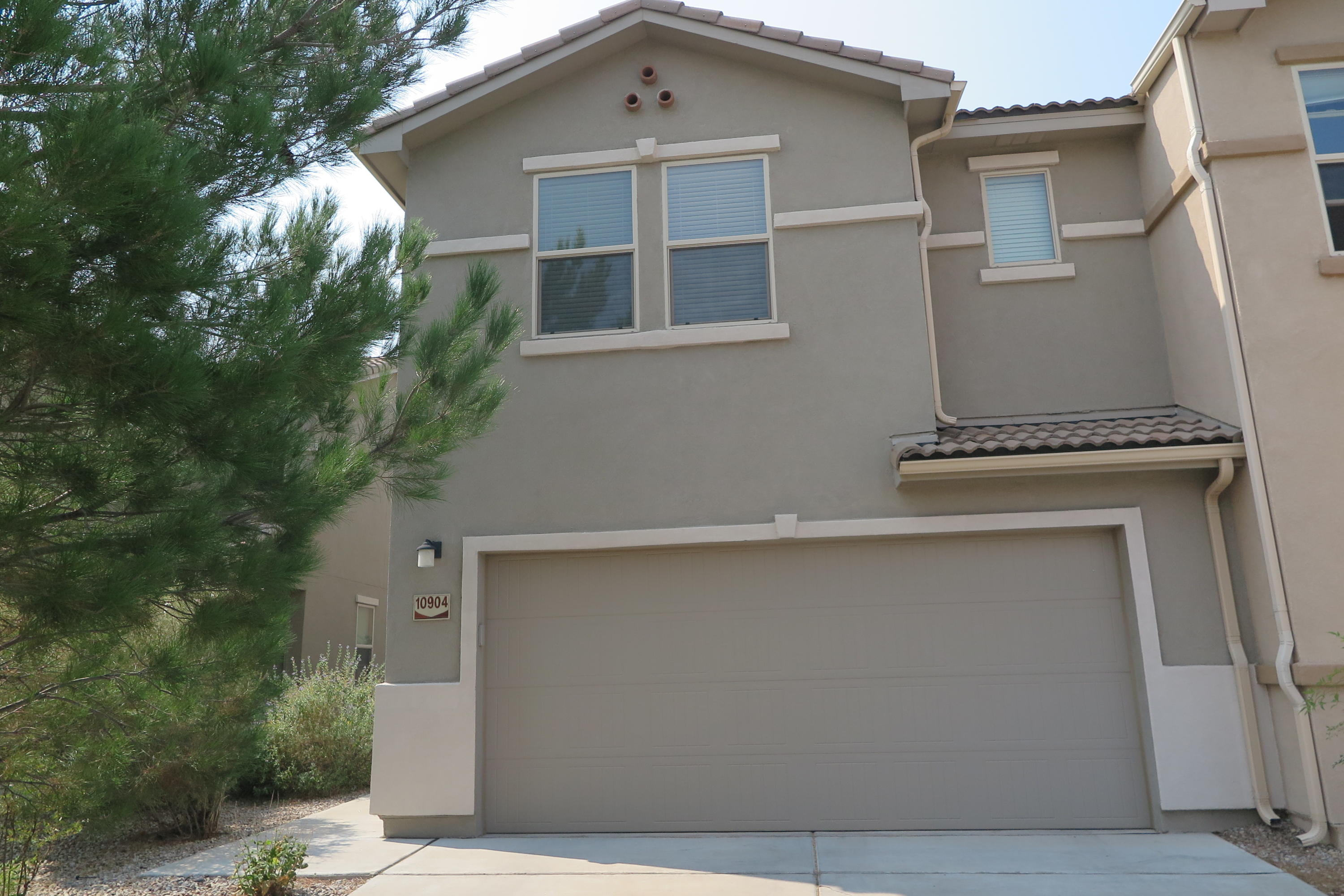 Wonderful 2 level town home, modern and maintenance free in gated community near Kirtland, Sandia and I-40. 2 living areas, one up other down. Ceramic tile floors lower level and wood laminate floors up. Large bedrooms, master with French doors, huge walk in closet & bath w/garden tub, sep shower and double sinks. Beautiful kitchen with Brk bar, pantry, stainless appliances (all stay) and tile floors & backsplash., all open to living area. Nite lights throughout, custom lighting, ceiling fans, linen closets, surround sound hookup, newer paint, Sep utility room  (washer/dryer stay). 1/2 Bath lower level and small foyer. Attached 2 car garage,  Nice yards, rear with turf and open patio. Super nice & modern design and touches.