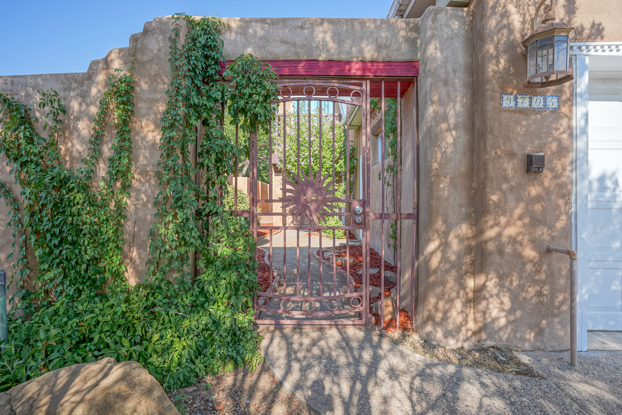 Come see this beautiful Northern New Mexico style home with lovely curb appeal in NW Albuquerque. This home features an inviting courtyard entry.  There are two bedrooms on the main floor, with the master on the upper floor.  The bathrooms are complete with Mexican tiles.  The kitchen looks onto an inviting living room with cathedral ceilings, saltillo tiles, and a wood burning kiva fireplace, and leads into the backyard courtyard that is great for BBQ's or just relaxing on a cool NM evening.  Conveniently located near parks, restaurants, shopping, & the freeway.
