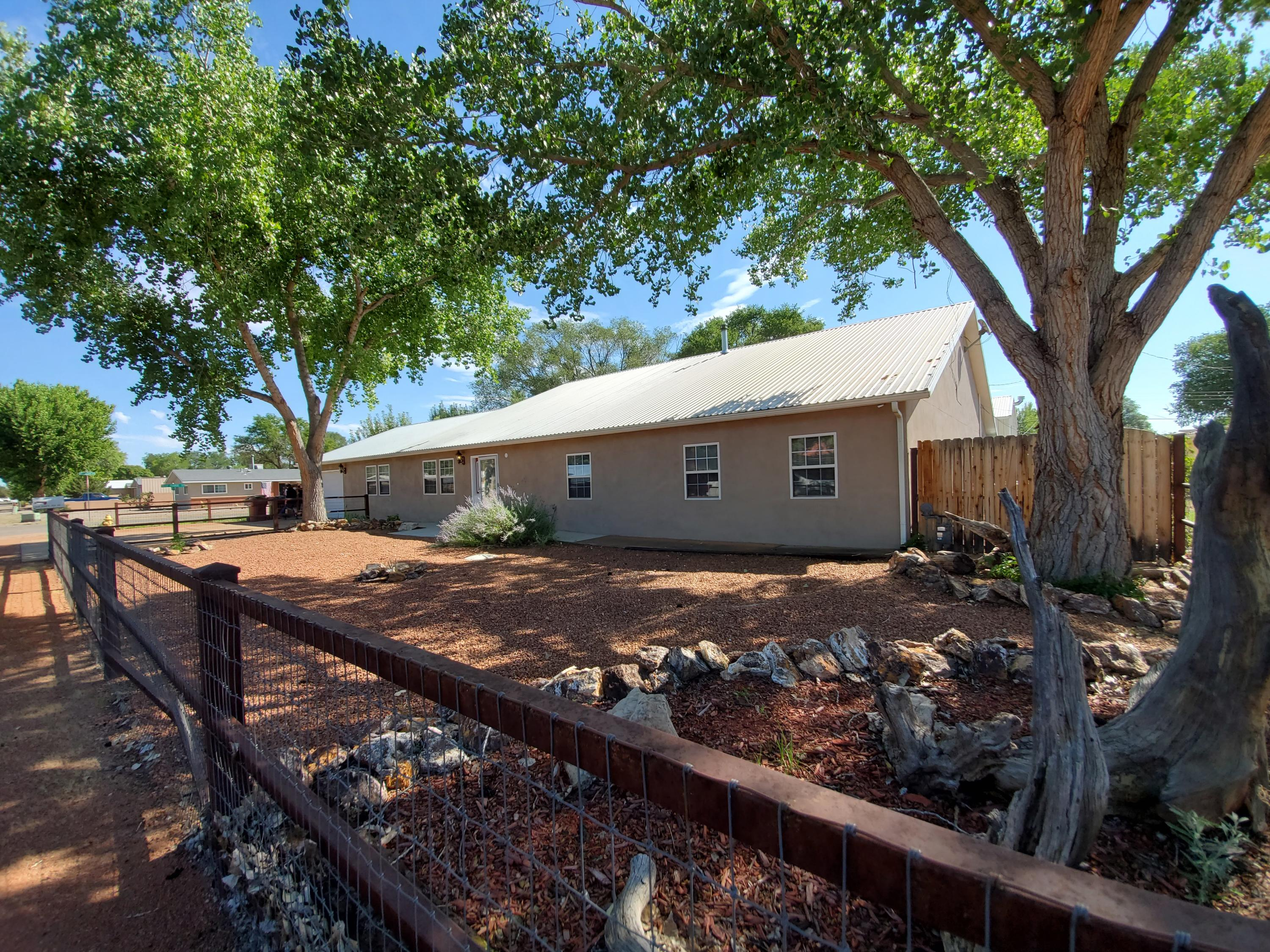 Spacious 3400 SF. custom ranch style home  on a half acre. 40x60 shop with 14x14 door & heating & air conditioning. Automatic Electric gate.  21x30 green house with 9x16 garden shed. Bring the farm with you, goat stalls, chicken coop & dog kennels. Outdoor patio with pond. Irrigation well. Alarm system. Radiant floor heat. Two commercial refrigerated cooling units. Heat on demand hot water heater. Water softener. Enjoy relaxing in hot tub in a 19X24 sunroom. Automatic sprinkler system. Laminate, & tile flooring. Large kitchen with hickory cabinets, wood stove & breakfast bar with an island. Recess lighting. Cozy living room with a vaulted ceiling. Bonus rooms are an office & mud room. Large attic. One car garage. Come & get away from the big city & make this fortress your forever home.