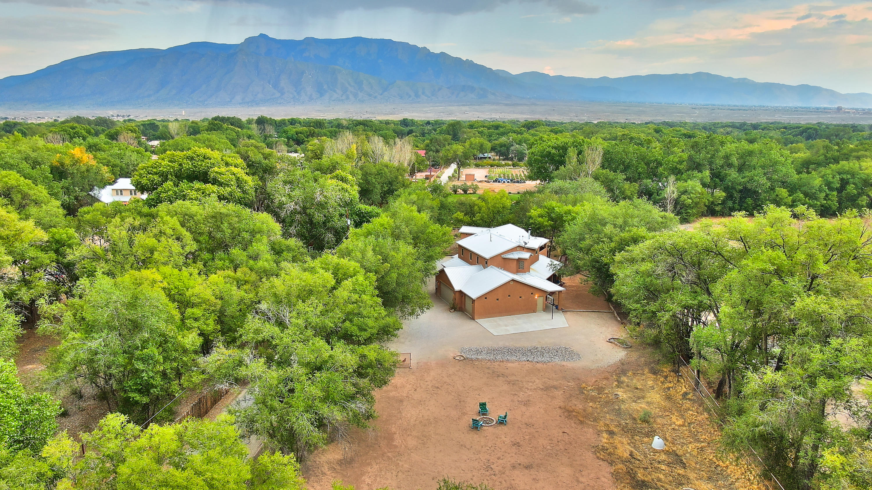 Fabulous custom home in desirable eastside, greenbelt location.  Northern NM in style,  this 2 story home sits on one piped, full acre.  Open, defined & light.  Wood floors, radiant floor & BB heat,  Refrigerated air. Great room w/high ceilings, vigas w/ T & G,fireplace/ pellet stove insert, & bancos.  Den w/wet bar,separate entry, BR & Bath.  Well designed kitchen.  island, gas cook top, downdraft, double oven, micro, & large pantry.  Access to outdoor kitchen w/wood burning fireplace.  Upstairs, MBR w/sitting area, balcony, garden bath, walk in closet.Three other generous size BR's, one with full bath, other two BR's share Jack & Jill bath.Service room is spacious,  three car gar.,set up well for a workshop.  Room for horse or vineyard to the west!  Lots of value,  a must to see!
