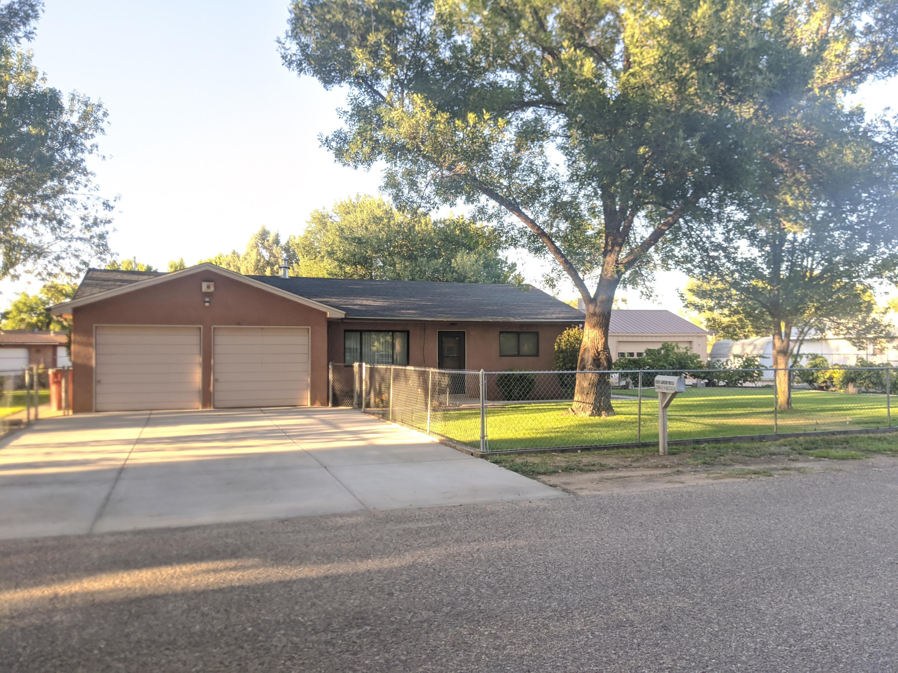 This charming home sits on a quiet street in the heart of Bosque Farms on a lush green half acre lot with mature shade trees. Inside you will find plenty of space with a formal living room, plus large family room for entertaining, open kitchen and dining area, and a heated sun room. In addition to the 2 car attached garage, there is a great approximately 20x30 insulated shop wired with 220, an additional storage building with built in chicken coops and green house, irrigation well and full sprinkler system for easy upkeep on the yard. This meticulously maintained home also has refrigerated air and a roof under a year old! Easy access to walking tails, bike path, and tennis courts, country living with all the conveniences!