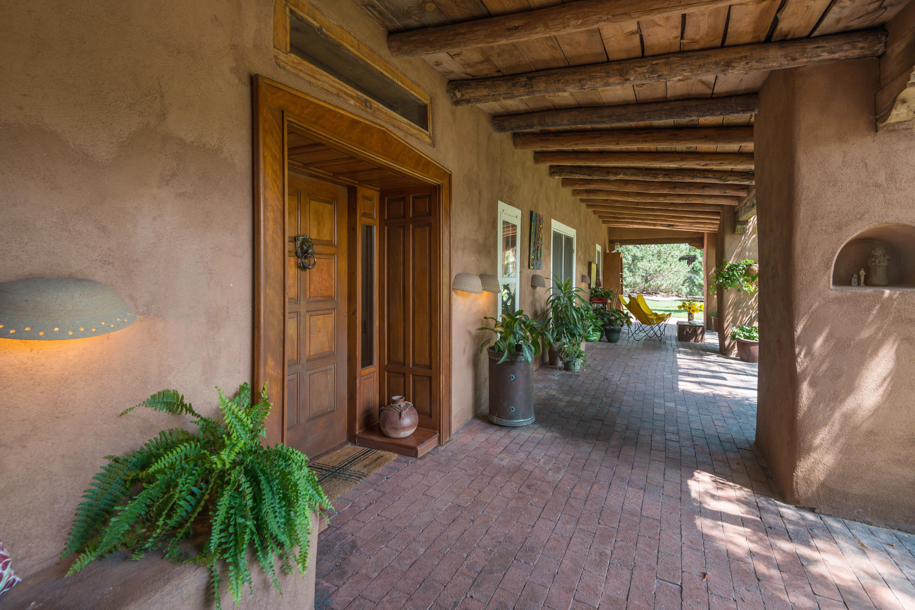 Character-filled historic adobe hacienda in the heart of Corrales set in a lush private setting bursting w/ rose gardens, cottonwoods & access to acequia trails. Step into another era w/ hand-crafted architectural detail, including stained glass windows, Talavera tile, hand-adzed beams & gorgeous brick & saltillo floors. 2 master suites in main house plus a charming separate studio w/ a 3/4 bath for guests or home office/business. Enter a world of serenity & quiet w/ 30'' thick adobe walls or relax outside on spacious patios. Horses welcome w/ on-site horse barn. Conveniently located in the Corrales Commercial zone, this extraordinary adobe could house an art gallery, restaurant or other retail establishment. The possibilities are endless! Corrales living at its very finest & most authentic.